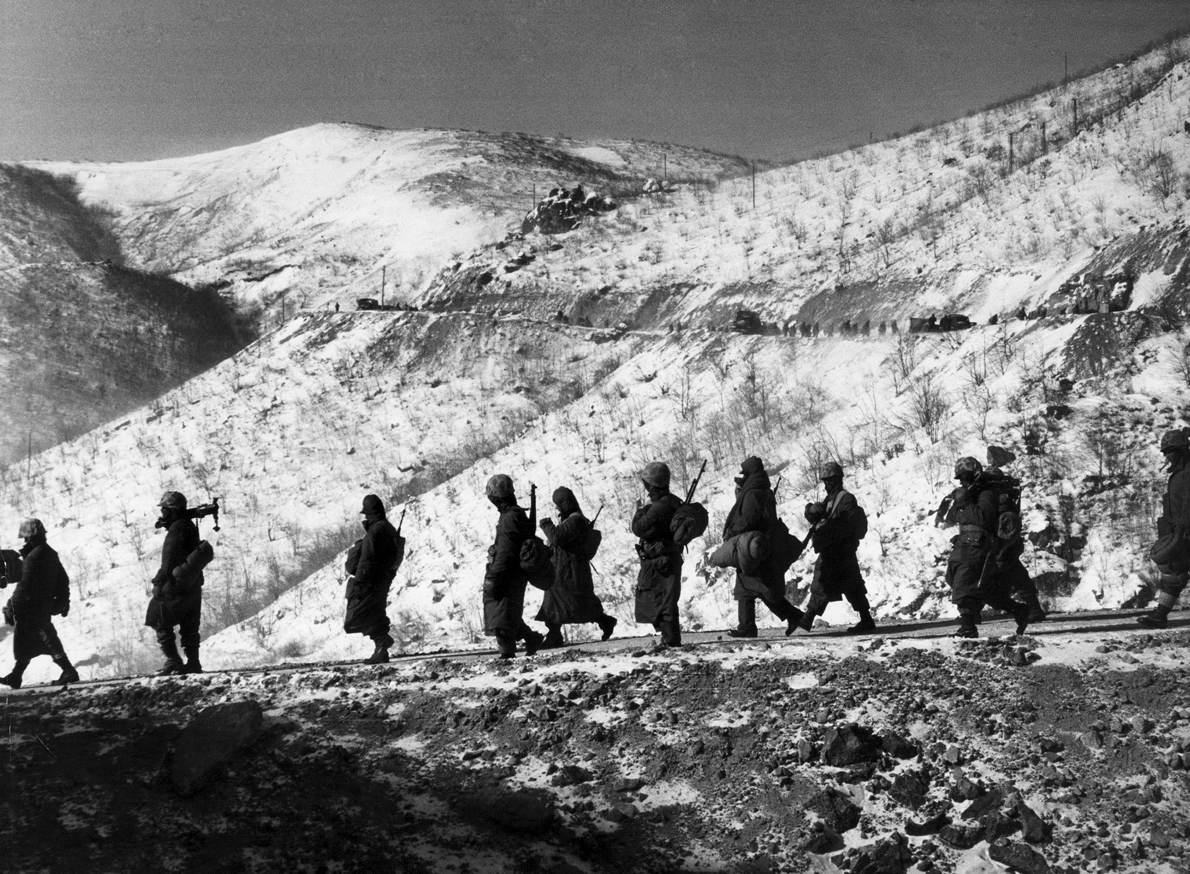 """American Marines march down a canyon road dubbed """"Nightmare Alley"""" during their retreat from Chosin Reservoir, Korea, 1950."""