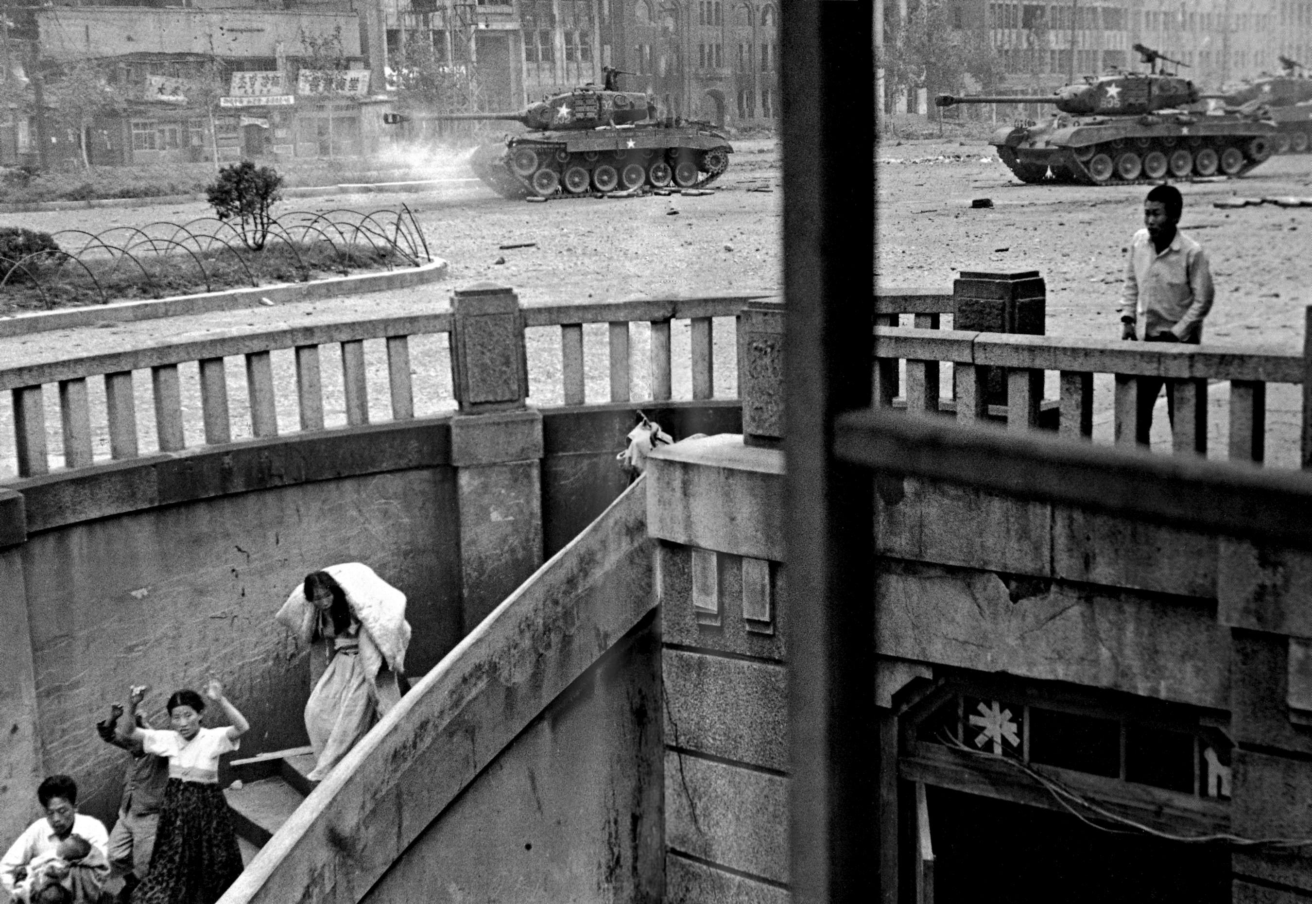 """""""This,"""" Duncan told LIFE.com of a picture made during the fight for Seoul, """"is the best picture I made in Korea of civilians — a family running down stairs, a father holding a baby, tanks firing away. Those tanks are taking fire from North Koreans right down the street!"""""""