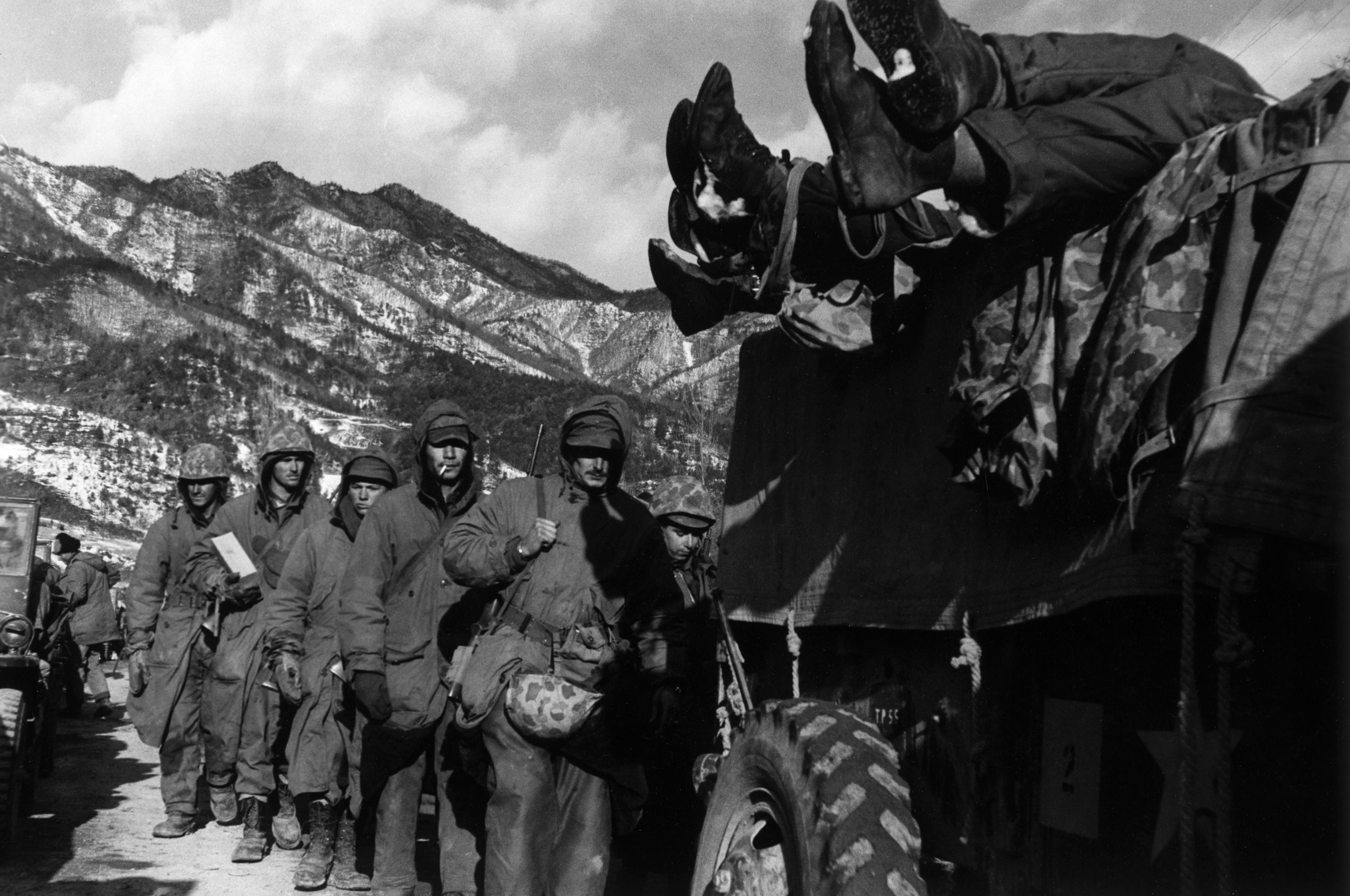 Marines file past a truck loaded with dead troops during the retreat from the Chosin Reservoir, December 1950.