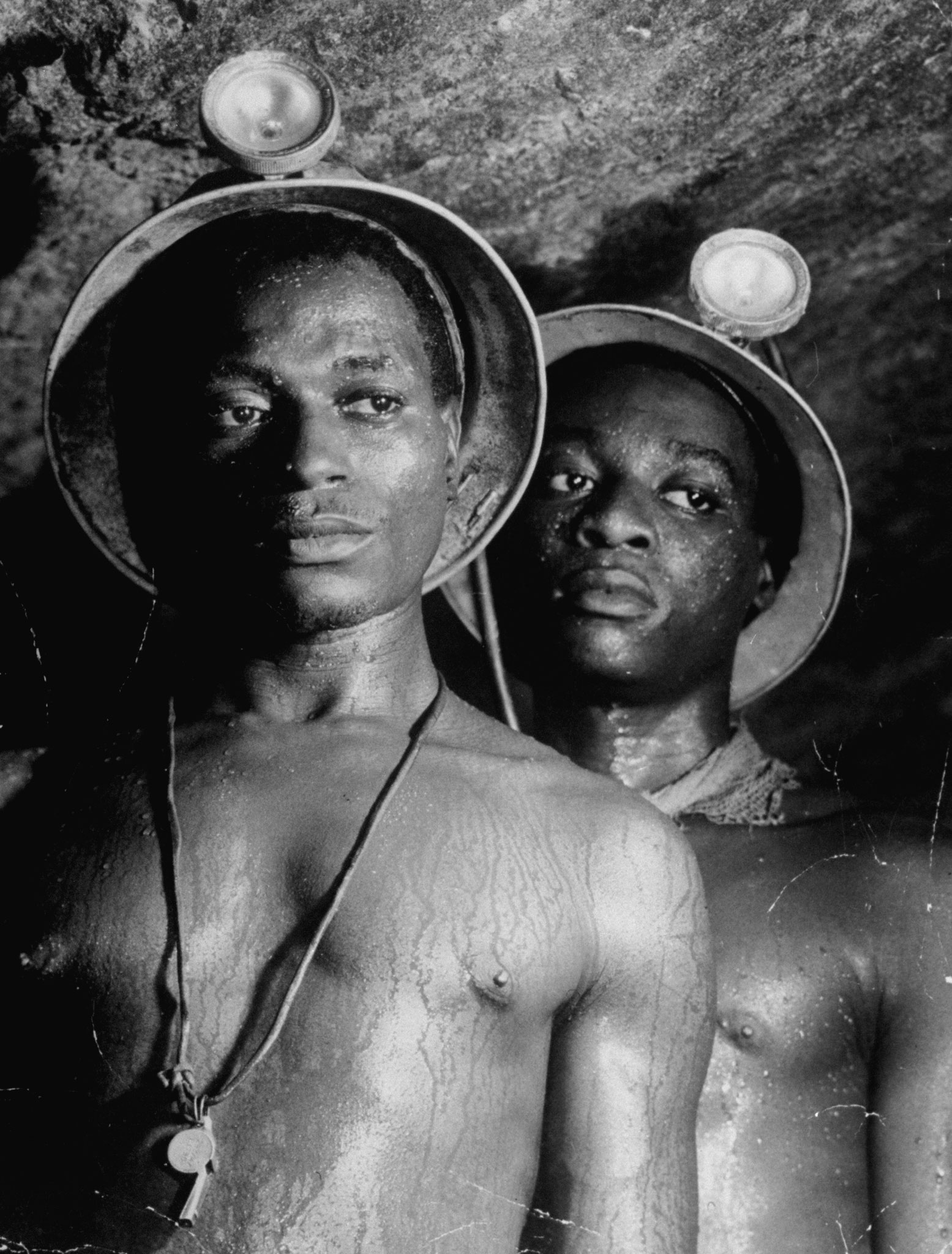 Caption from LIFE. Gold miners nos. 1139 and 5122, both Mndaus, stand sweating in 95 degree heat of a tunnel in Johannesburg's Robinson deep mine, more than a mile underground.