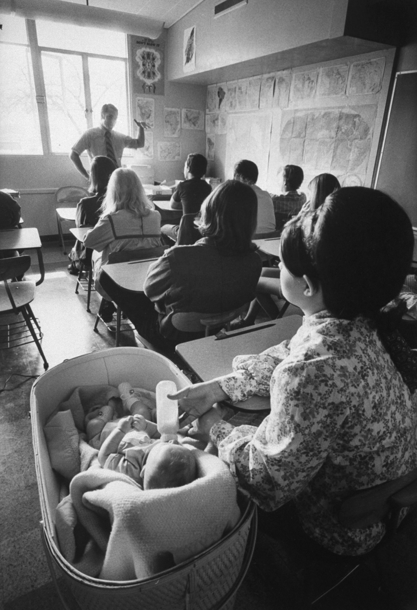 <b>Caption from LIFE.</b> During a social studies class, Cheryl Gue, 17, quiets her son Michael with a bottle. Although the sound of crying babies is a normal disruption at Citrus, the more vocal ones are usually hustled out of class. The school is equipped with playpens, cribs and toys. The mothers are required to come to school for the morning child-care courses, but may study academic subjects at home.