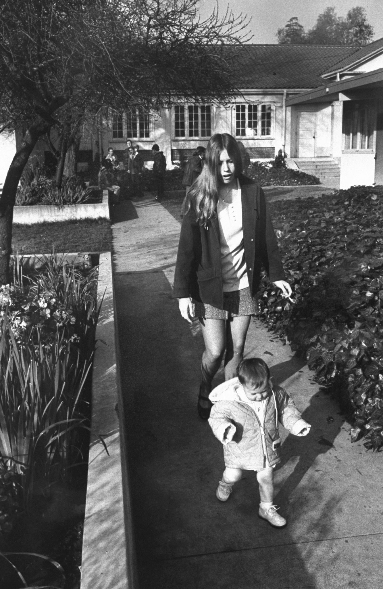 <b>Caption from LIFE.</b> In the courtyard outside the school, Vicki Conger, 17, takes a stroll with her 13-month-old daughter, Shawn Michelle.