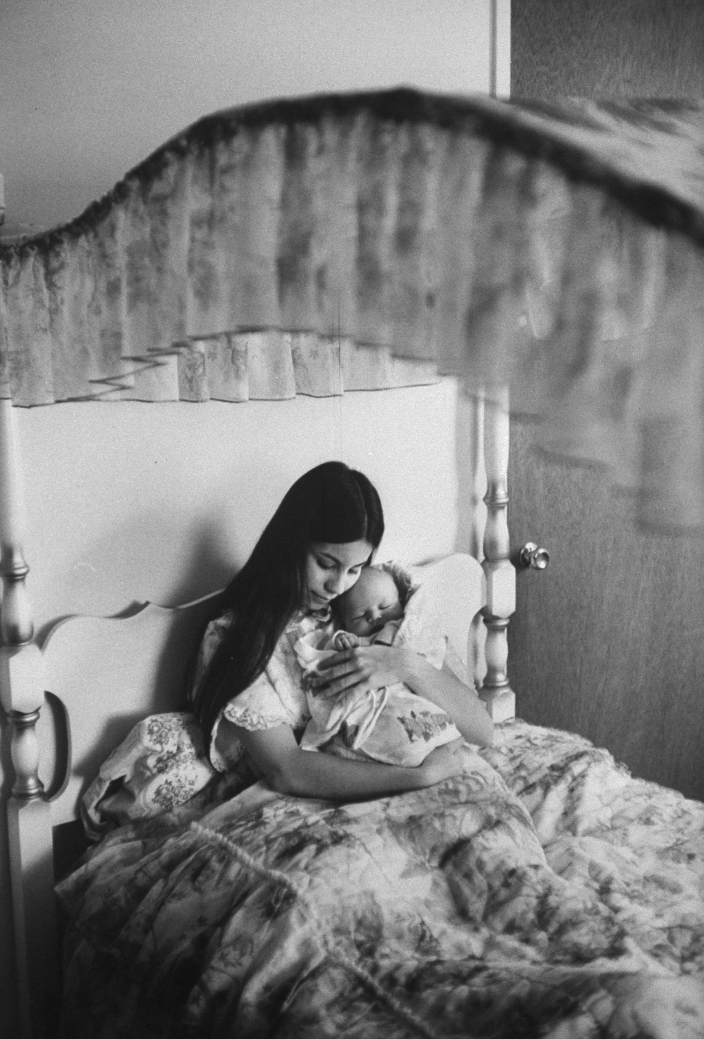 <b>Caption from LIFE.</b> In the canopied bed where she has slept since childhood, Judy cuddles her son Dylan, who was born in late February. 'My son may have been unplanned,' Judy says, 'but he is not unloved.