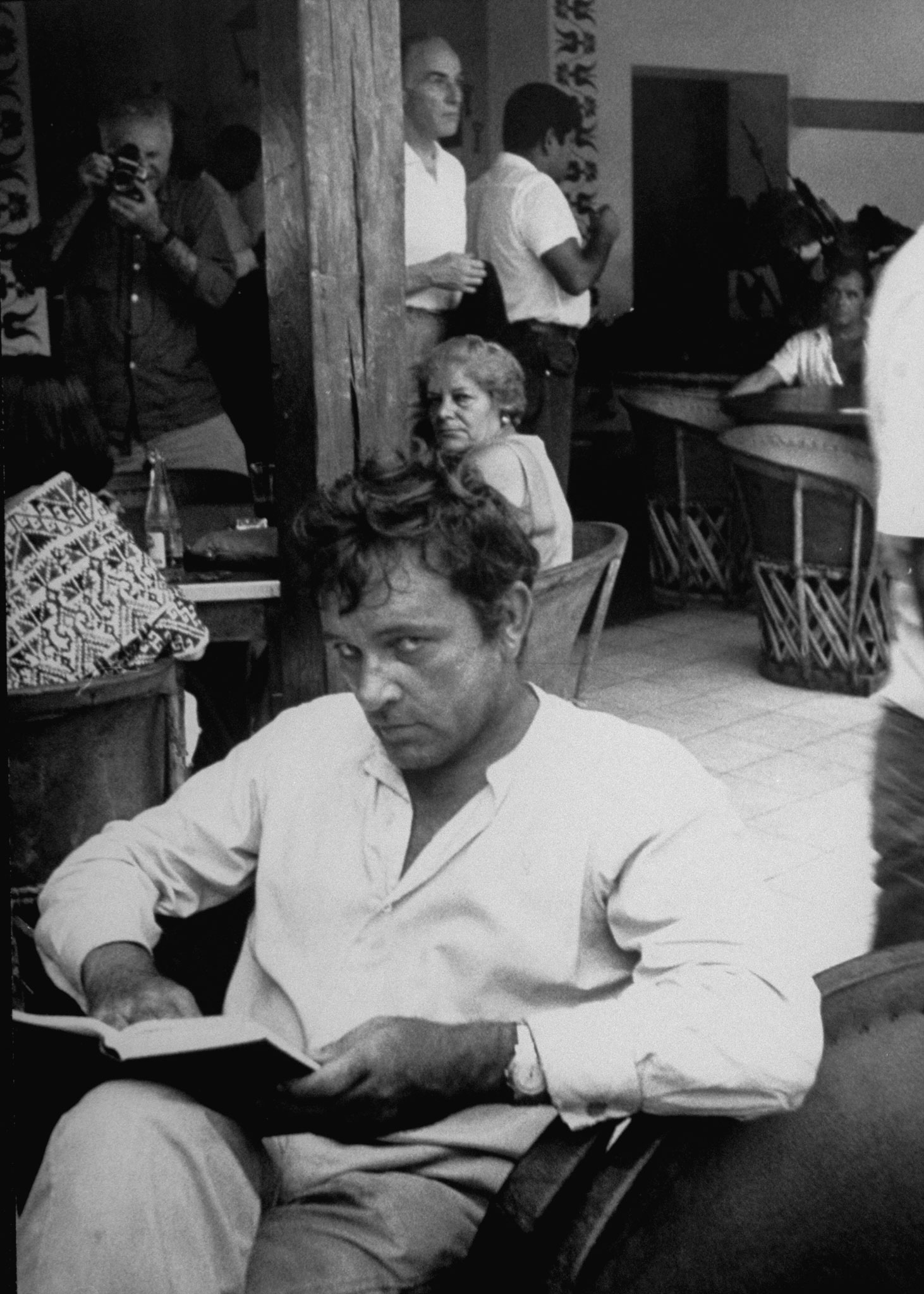 Richard Burton, who was nominated seven times. Pictured relaxing with a book  in Cantina while on location filming <i>The Night of the Iguana</i>, 1963.