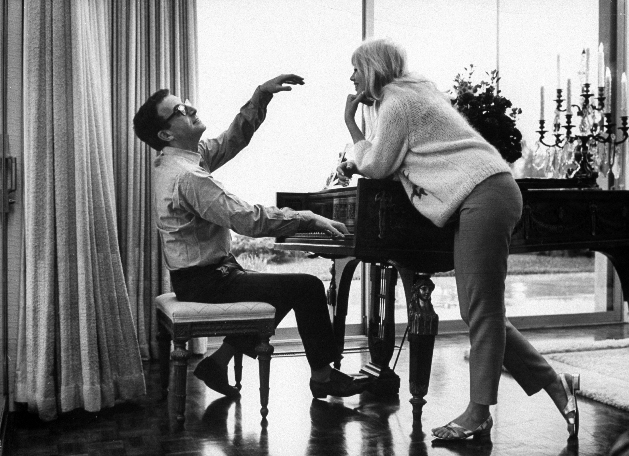 Peter Sellers, who was nominated three times. Pictured playing the piano at home with his wife, Britt Ekland, in Beverly Hills, 1964.