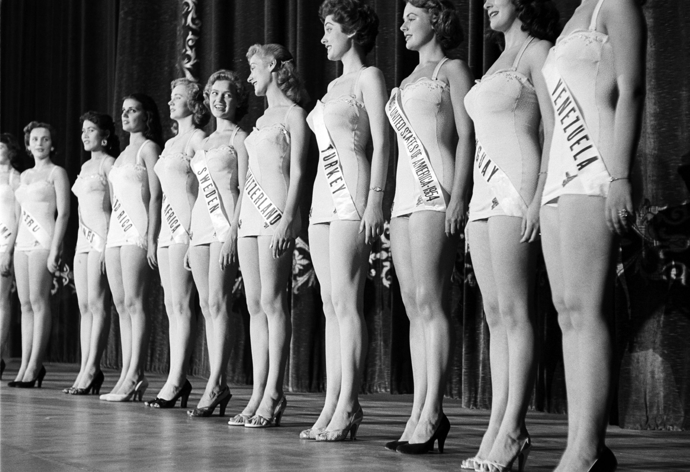 Miss Sweden and Miss Switzerland exchange friendly smiles at the 1953 Miss Universe pageant.