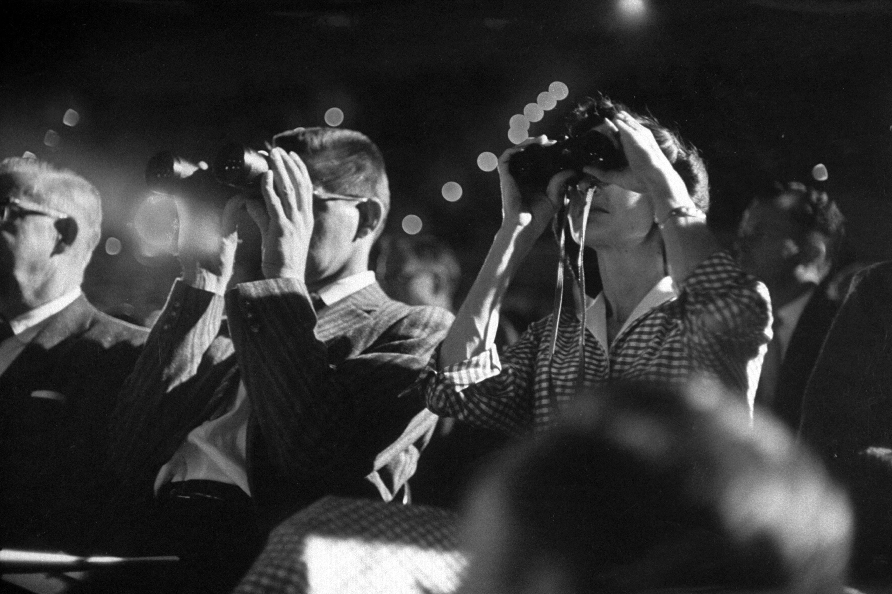 Audience members with binoculars during the 1957 Miss Universe contest.