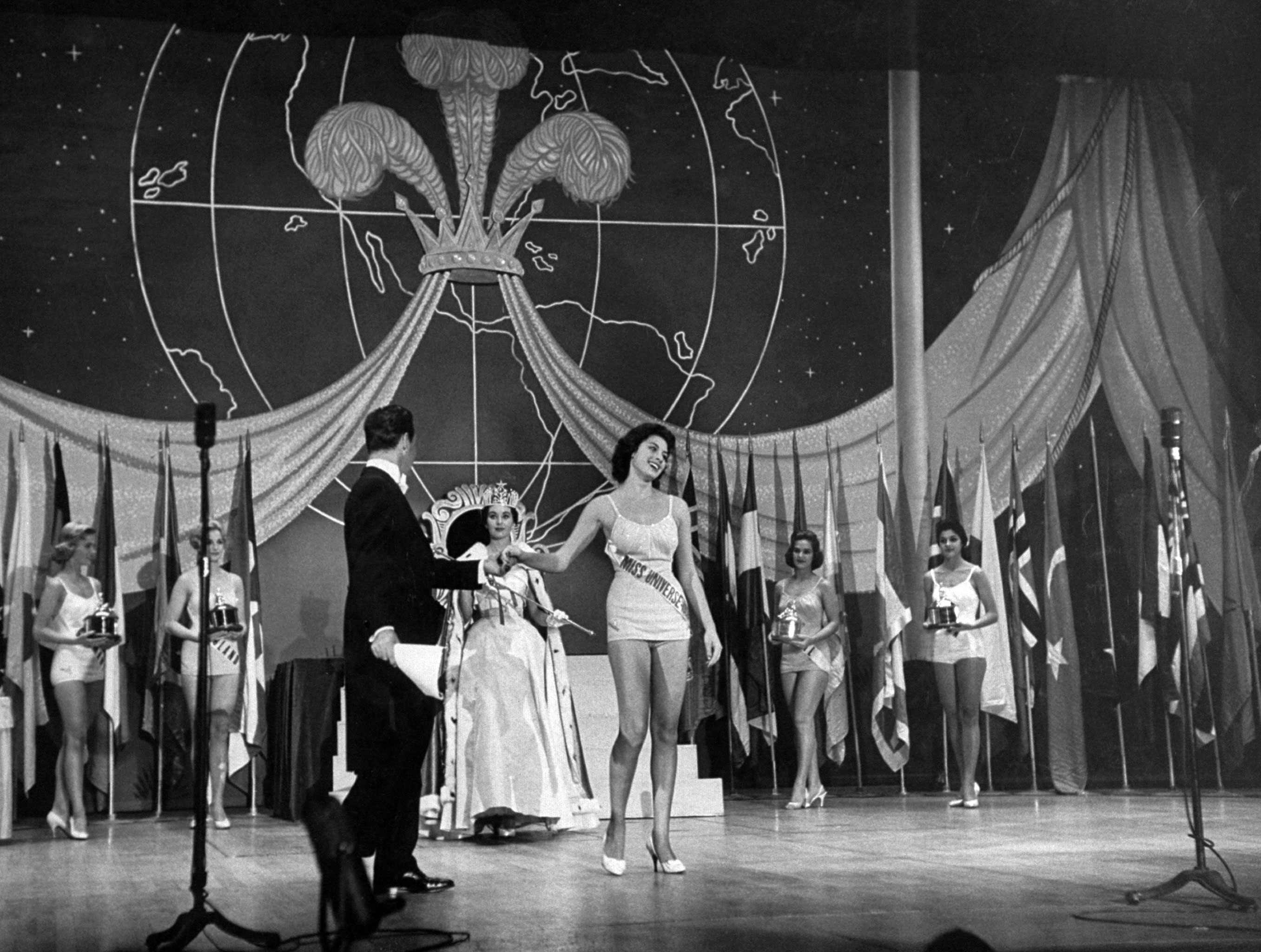Winner Gladys Zender being crowned by former Miss Universe Carol Morris, 1957.