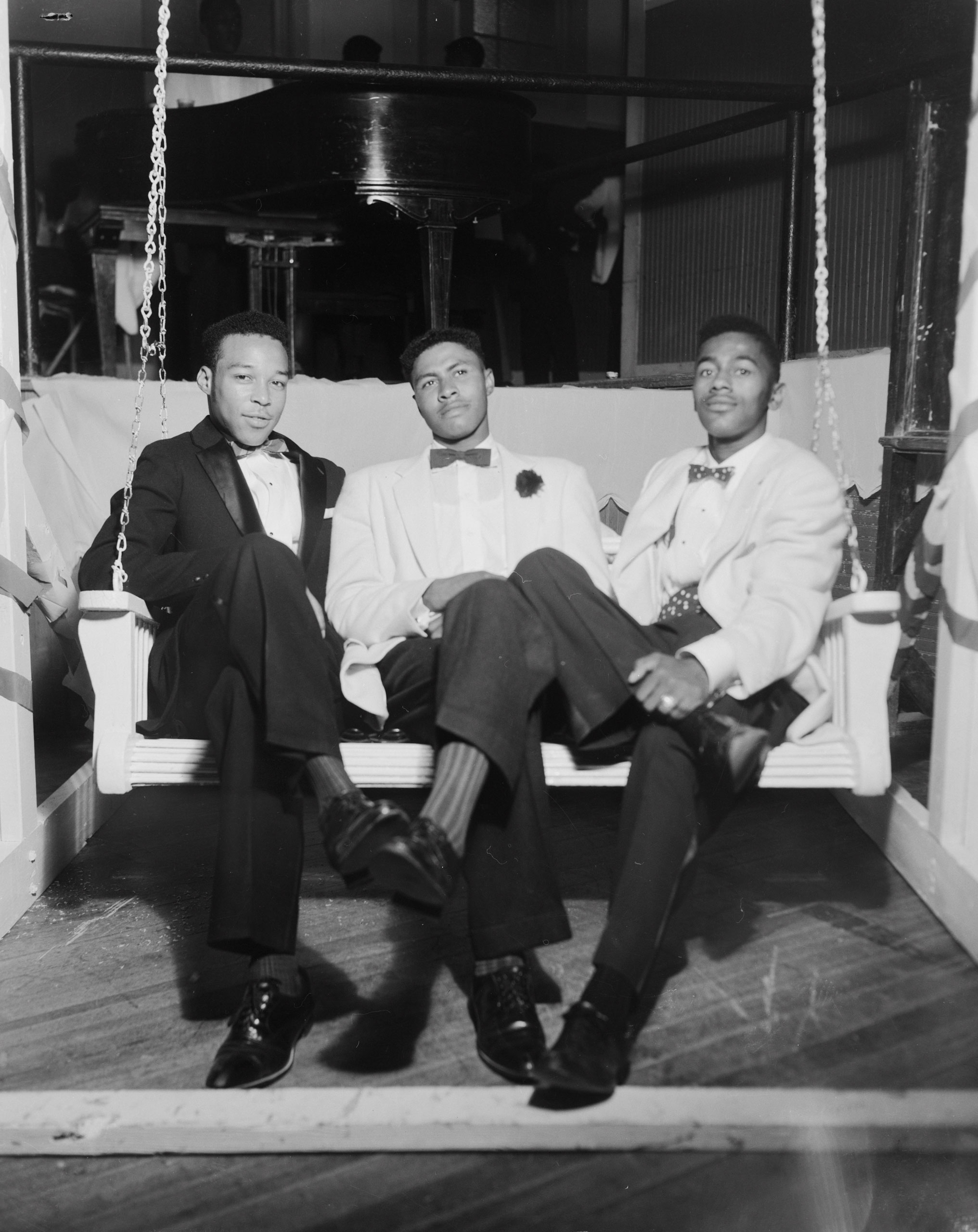 Douglas Burns, Charles Henry Sayles, and Alfred A. Neal sitting on a porch swing, 1958.