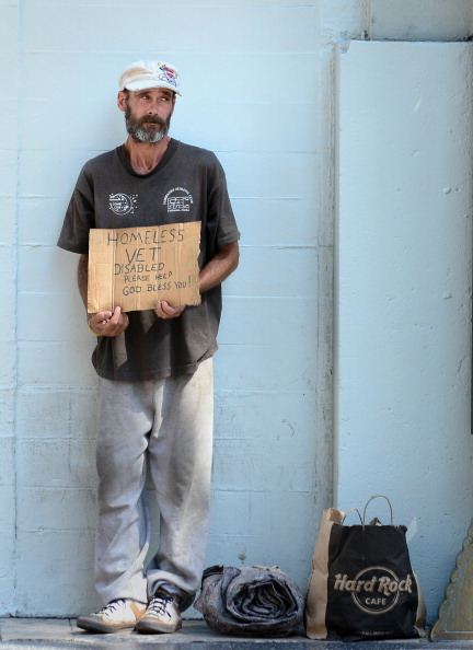 A homeless war veteran explains his plight hoping for assistance while standing along Hollywood Boulevard in Hollywood, California, on August 22, 2012. The US Congress's budget analysts said today that current plans designed to slash the budget deficit after January 1 will plunge the country into recession and push up joblessness. AFP PHOTO / Frederic J. BROWN        (Photo credit should read FREDERIC J. BROWN/AFP/GettyImages)