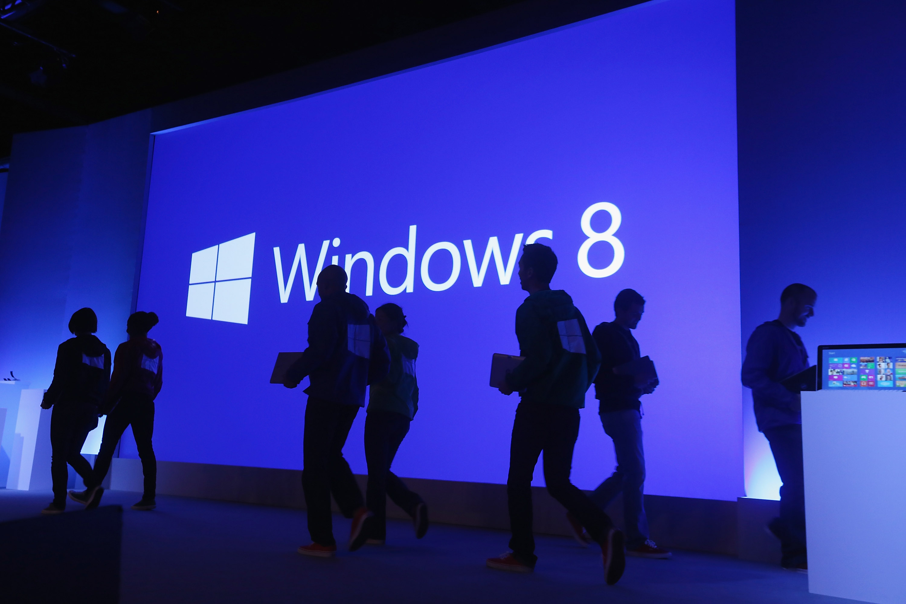 People walk past a display at a press conference unveiling the Microsoft Windows 8 operating system on October 25, 2012 in New York City.