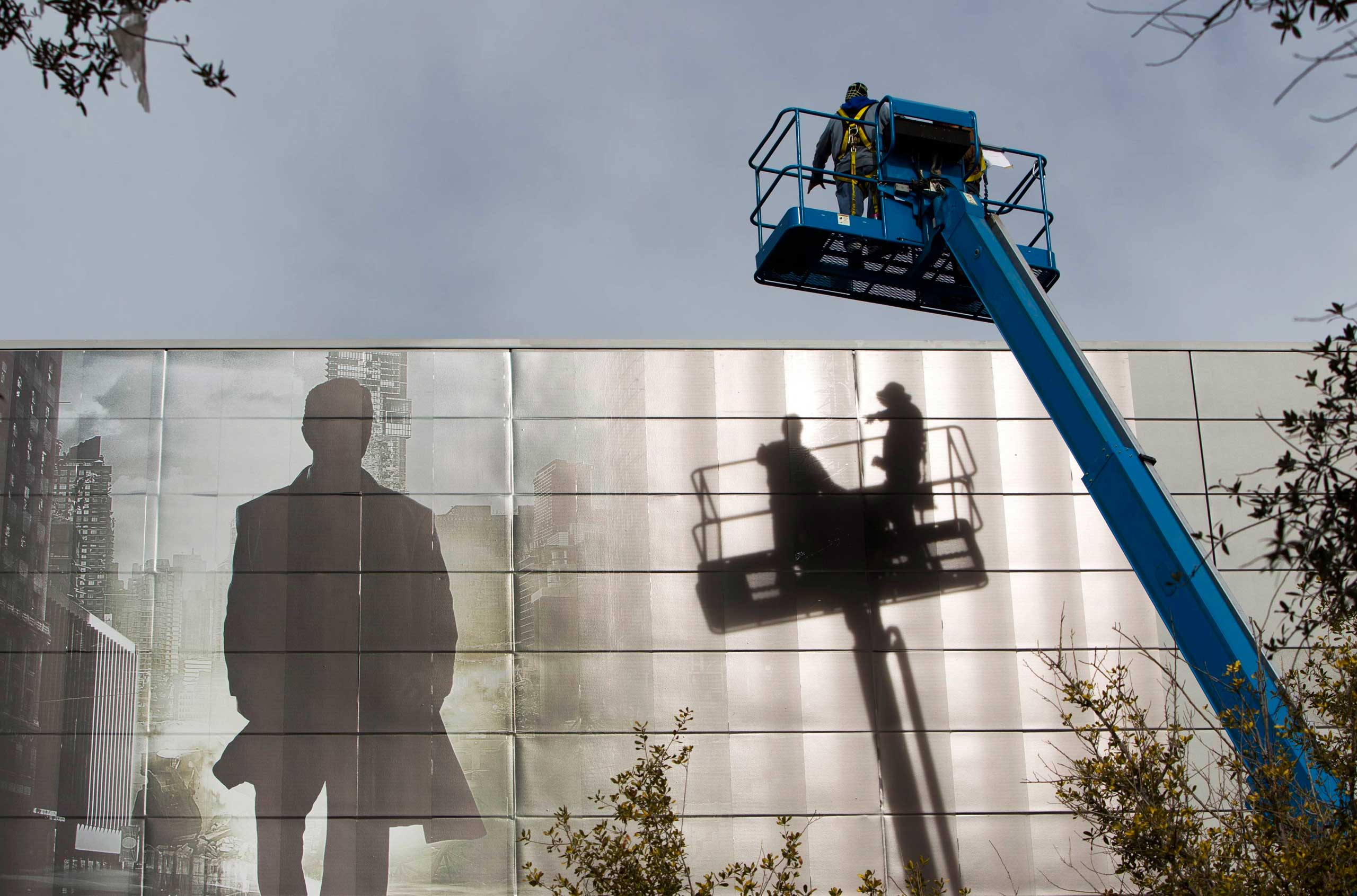 Workers install an advertisement for a new S'UHD TV from Samsung Electronics on the side of the Las Vegas Convention Center on Jan. 4, 2015.
