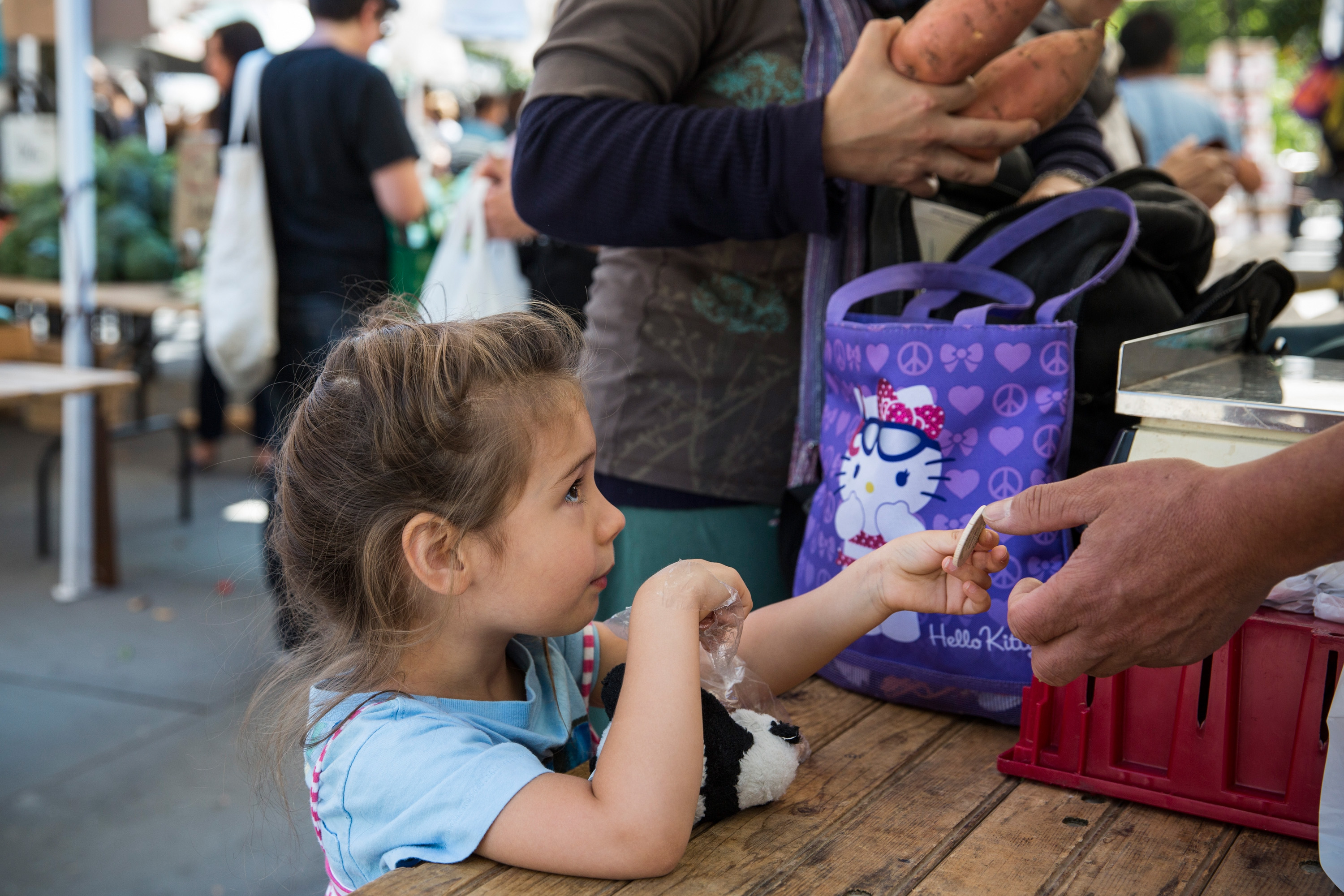A girl pays for her mother's groceries using Electronic Benefits Transfer (EBT) tokens, more commonly known as Food Stamps, at the GrowNYC Greenmarket in Union Square on September 18, 2013 in New York City.