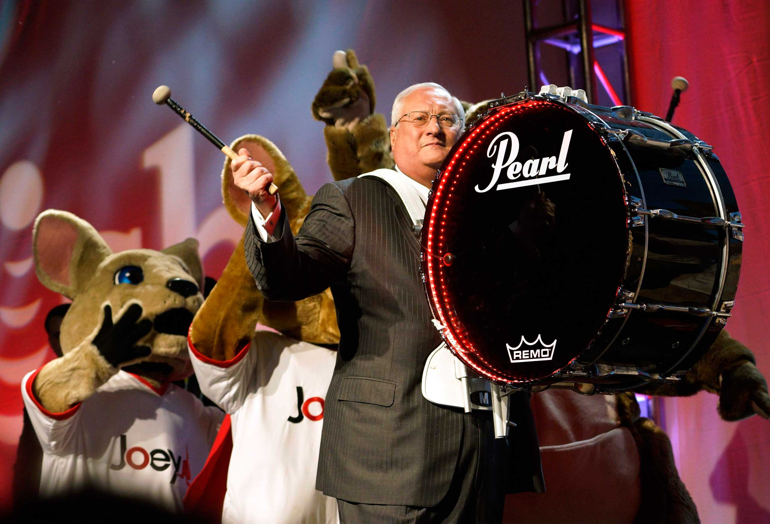 Joe Clayton, CEO of Dish, arrives on stage banging a bass drum followed by company mascots during the Dish news conference on Jan. 5, 2015.