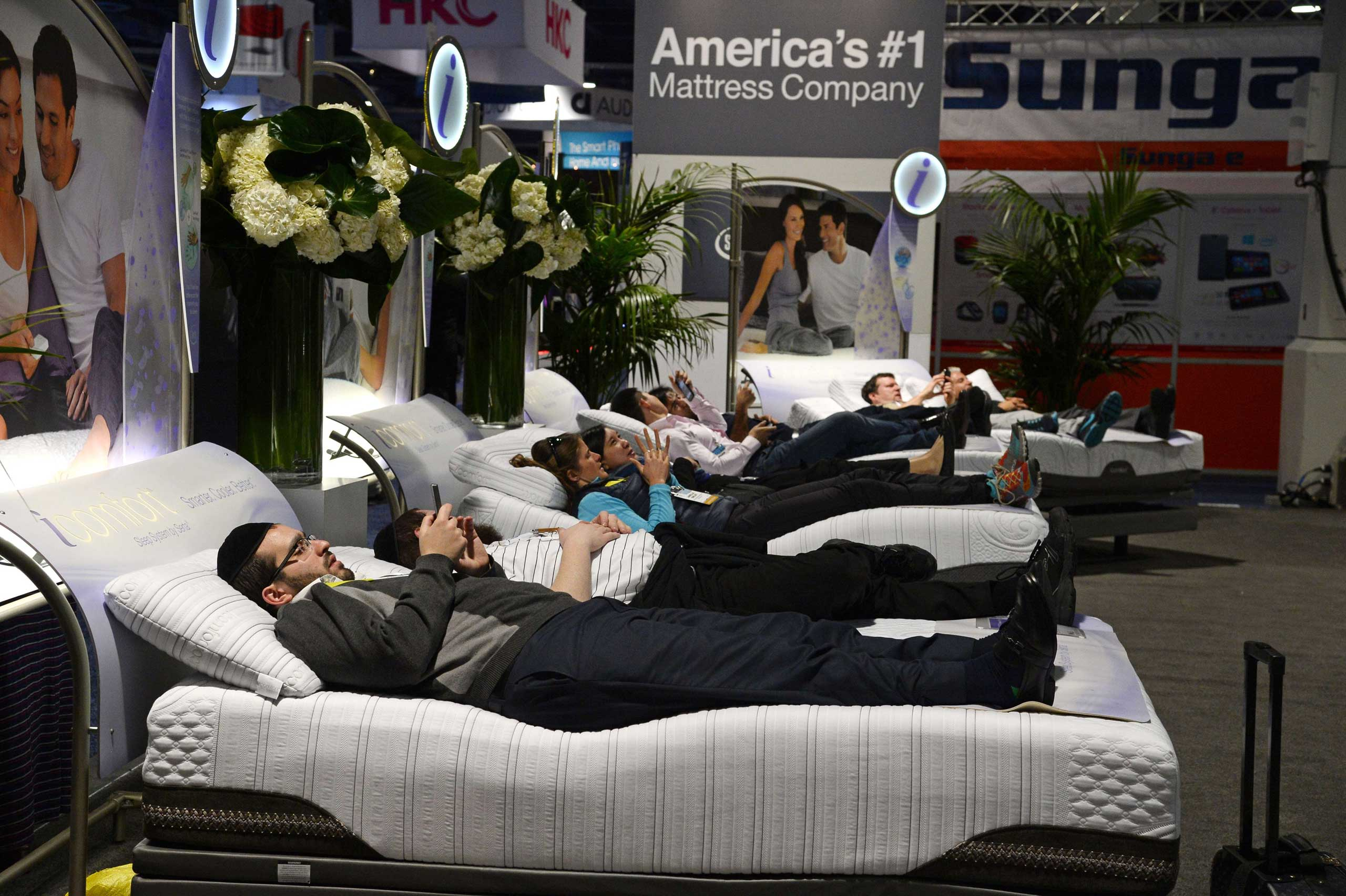 Attendees lay on Serta mattresses at the Serta stand on Jan. 6, 2015.