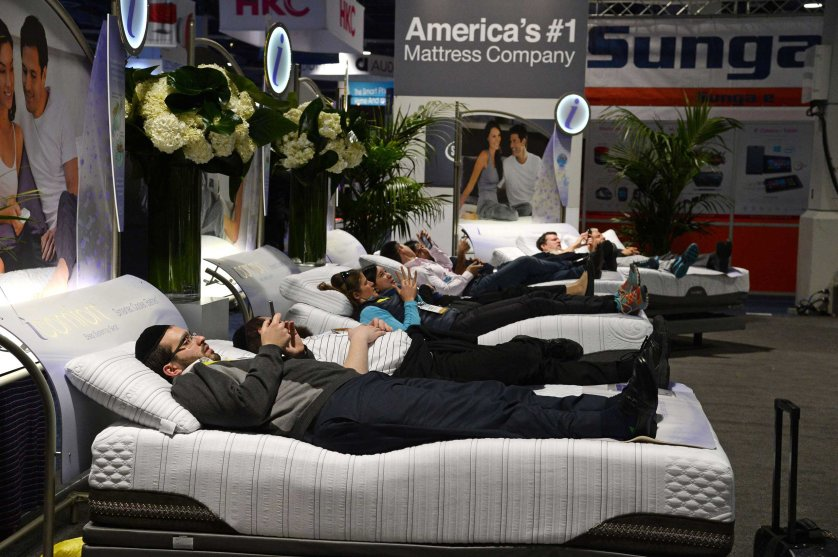 Attendees lay on Serta mattresses at the Serta stand on Jan. 6, 2015 at the Consumer Electronics Show in Las Vegas.