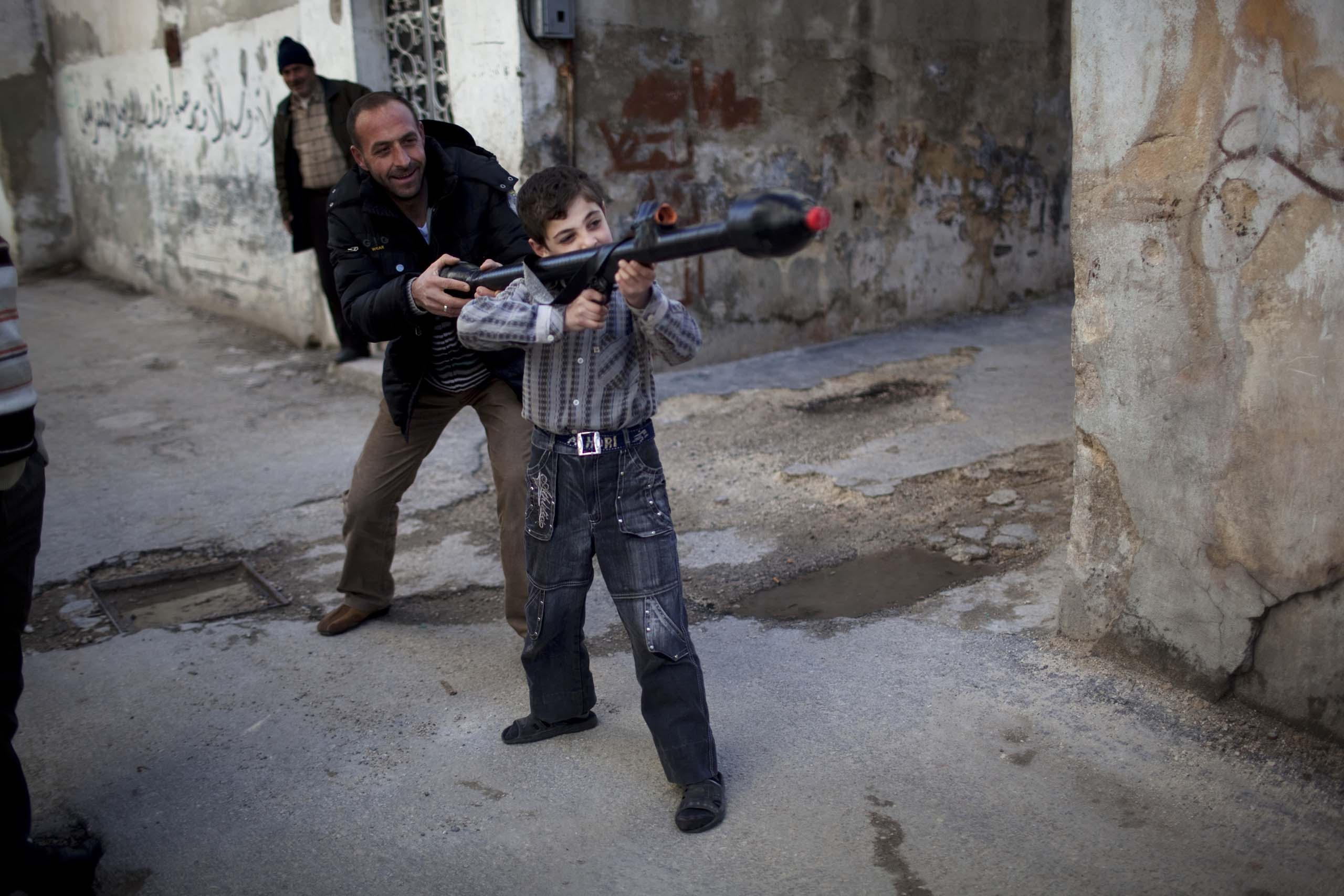A man teaches a child to use a toy grenade launcher in Idlib, Syria.