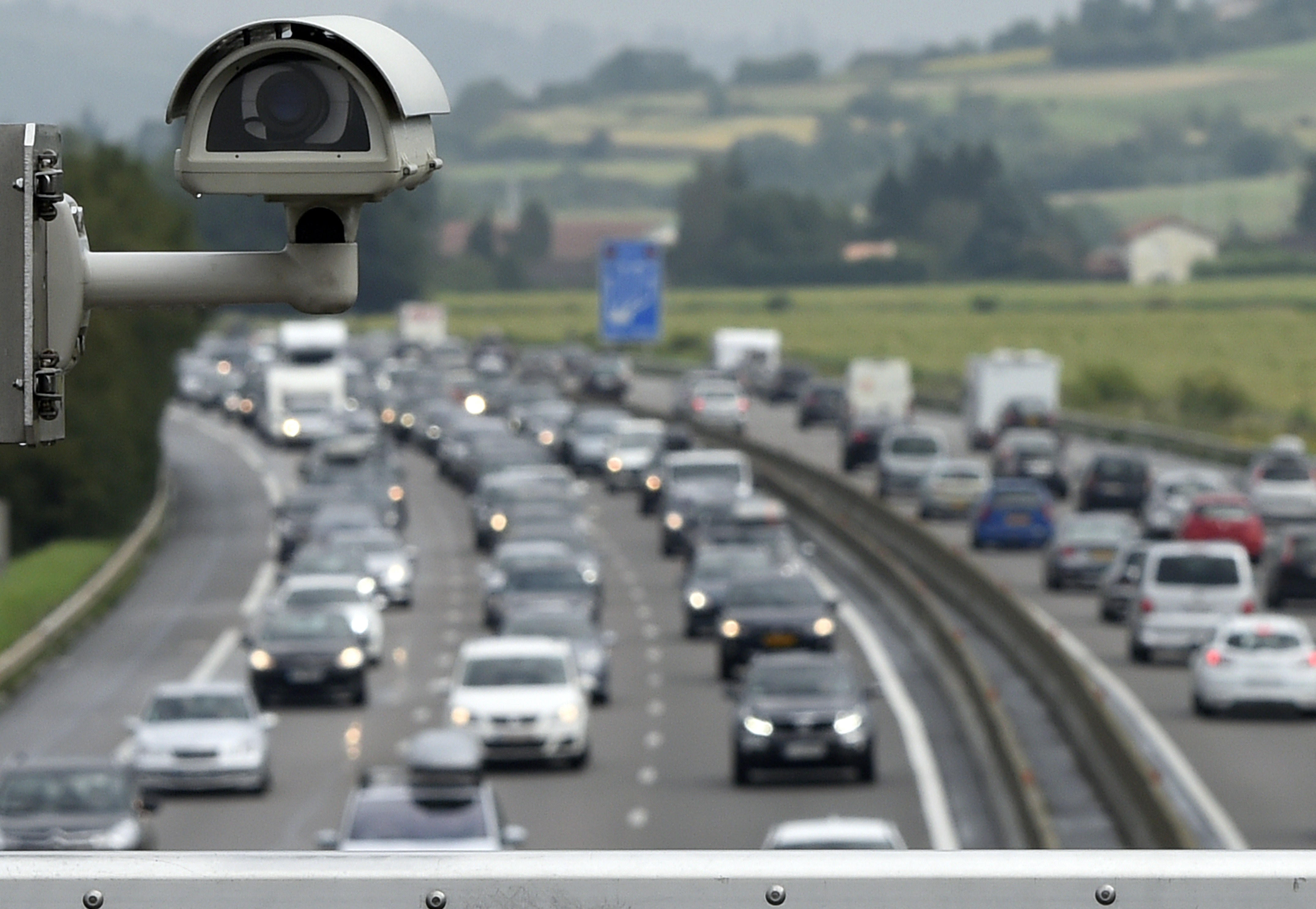 Motorists drive in traffic on the A7 motorway under a bridge where a security camera is set on August 2, 2014 at the toll station of Vienne, southeastern France.