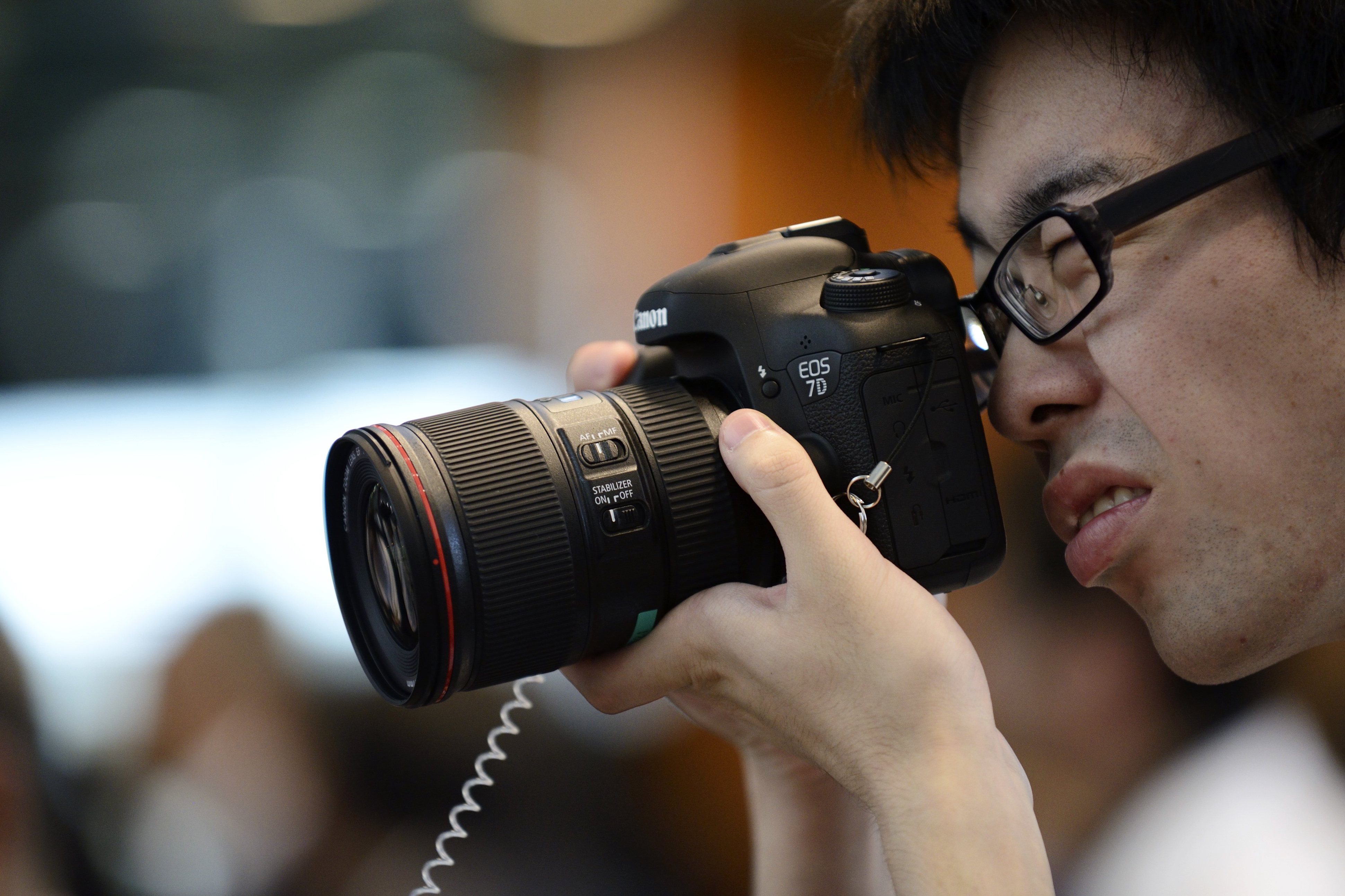 An attendee tries the Canon Inc. EOS 7D Mark II digital single lens reflex (DSLR) camera during its unveiling in Tokyo, Japan, on Tuesday, Sept. 16, 2014.