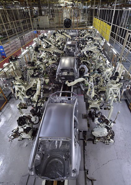 A general view shows the body welding workshop which uses automated welding machine robots that assemble automobile bodies called white body (body before painting) at Toyota Motor's Tsutsumi plant in Toyota, Aichi prefecture on December 4, 2014.  AFP PHOTO / KAZUHIRO NOGI        (Photo credit should read KAZUHIRO NOGI/AFP/Getty Images)