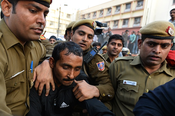 Indian police escort Uber taxi driver and accused rapist Shiv Kumar Yadav, center, following his court appearance in New Delhi on Dec. 8, 2014