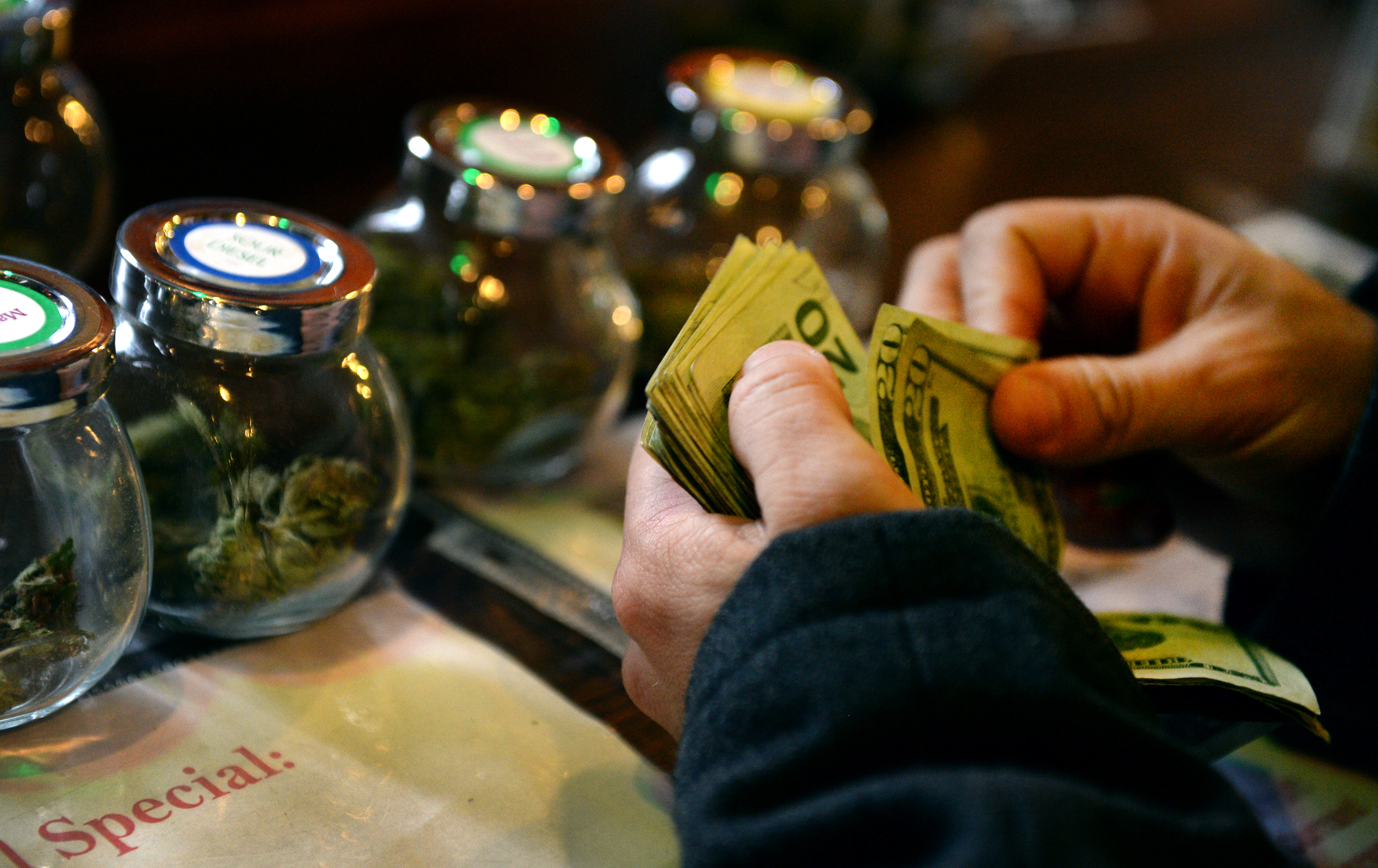A tour member purchases marijuana at La Conte's Clone Bar & Dispensary during a marijuana tour in Denver on Dec. 6, 2014