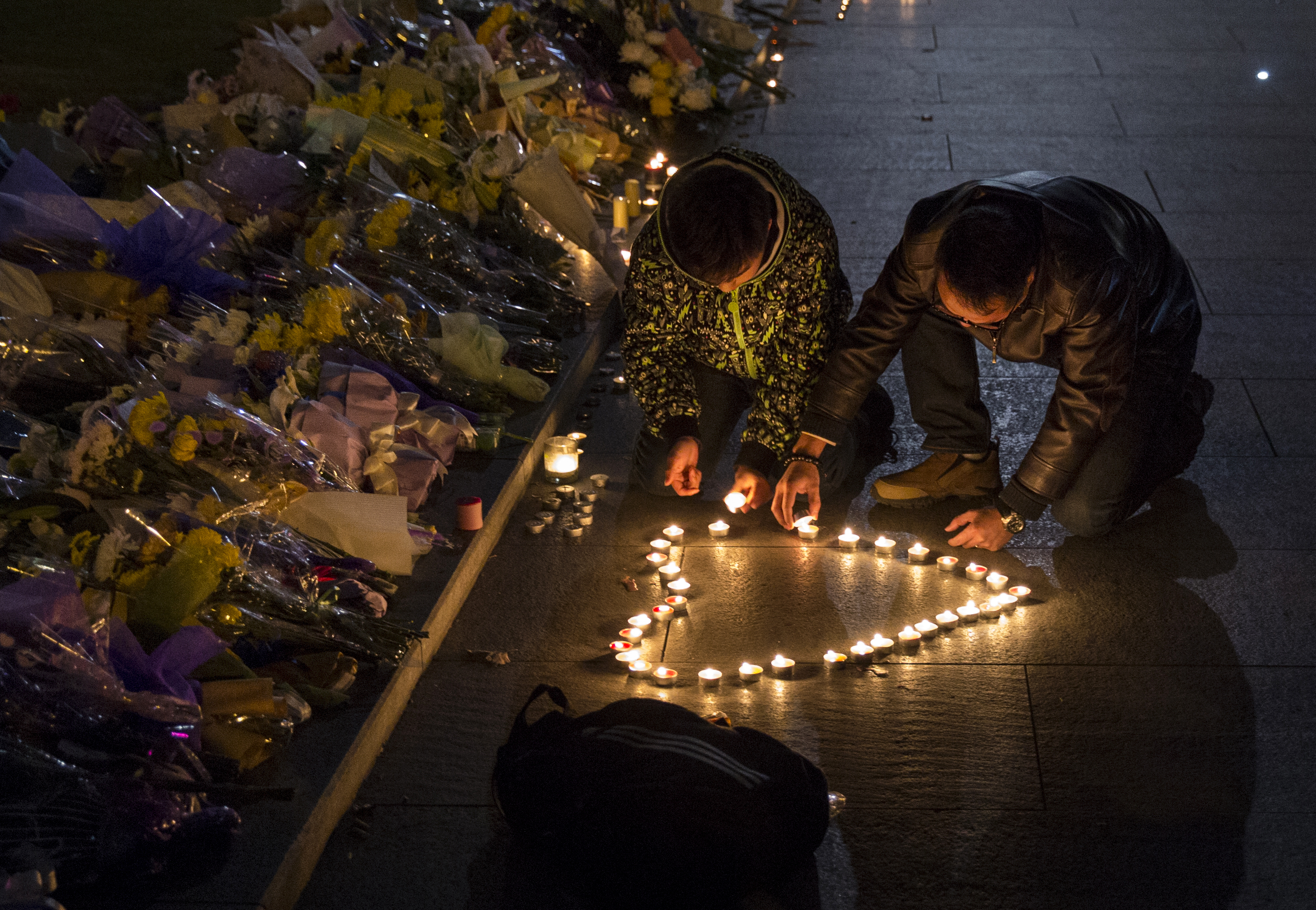 Mourners light candles in the shape of a heart at a makeshift memorial at the site of a stampede on January 1, 2015 on the Bund in Shanghai, China. More than 35 people died and dozens were injured during a stampede at a New Years eve celebration late December 31, 2014.