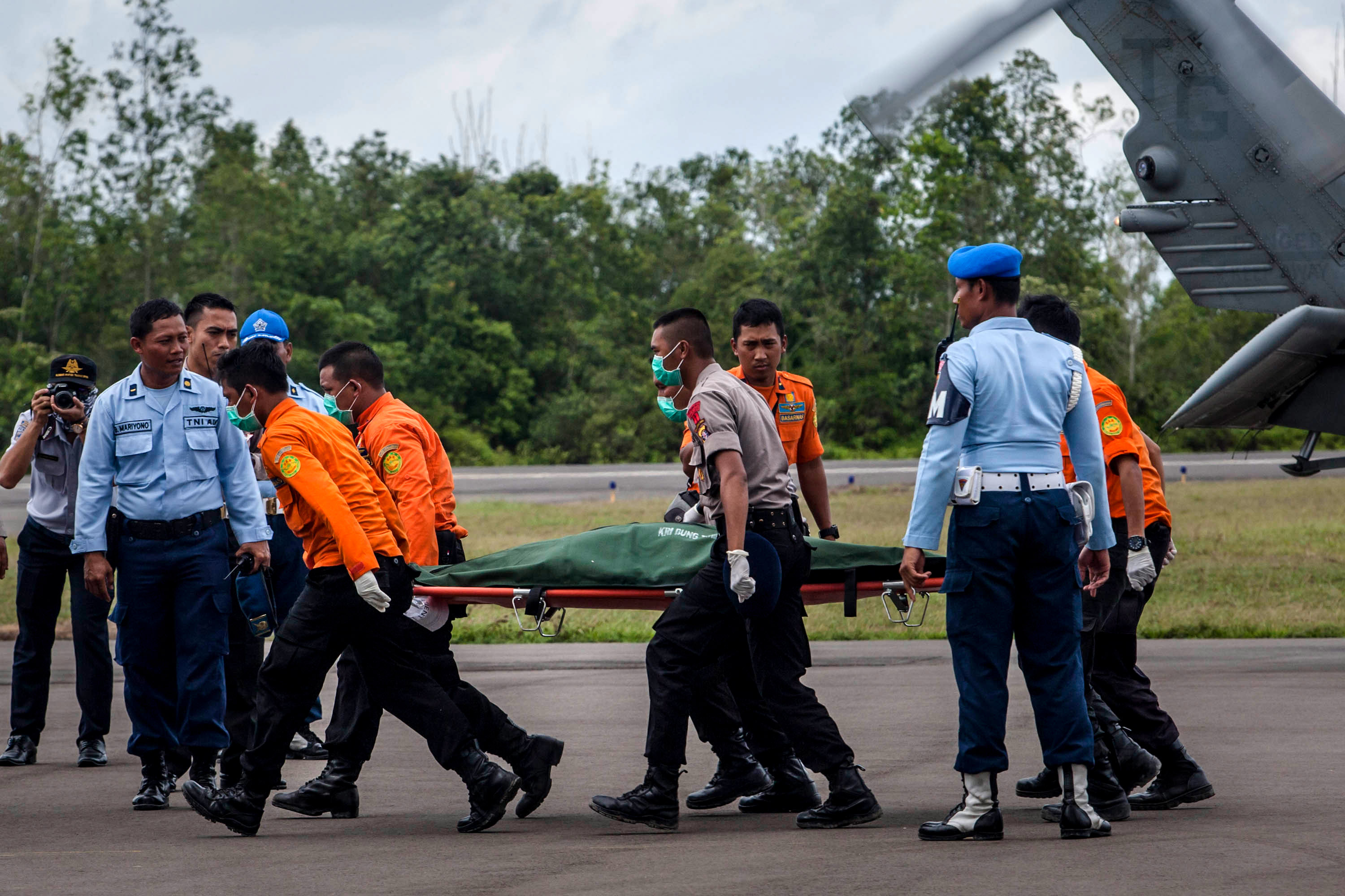 Members of an Indonesian search and rescue team carry the body of a victim of the AirAsia flight QZ8501 crash from a USS navy helicopter at Iskandar Airbase on January 02, 2015 in Pangkalan Bun, Central Kalimantan, Indonesia.