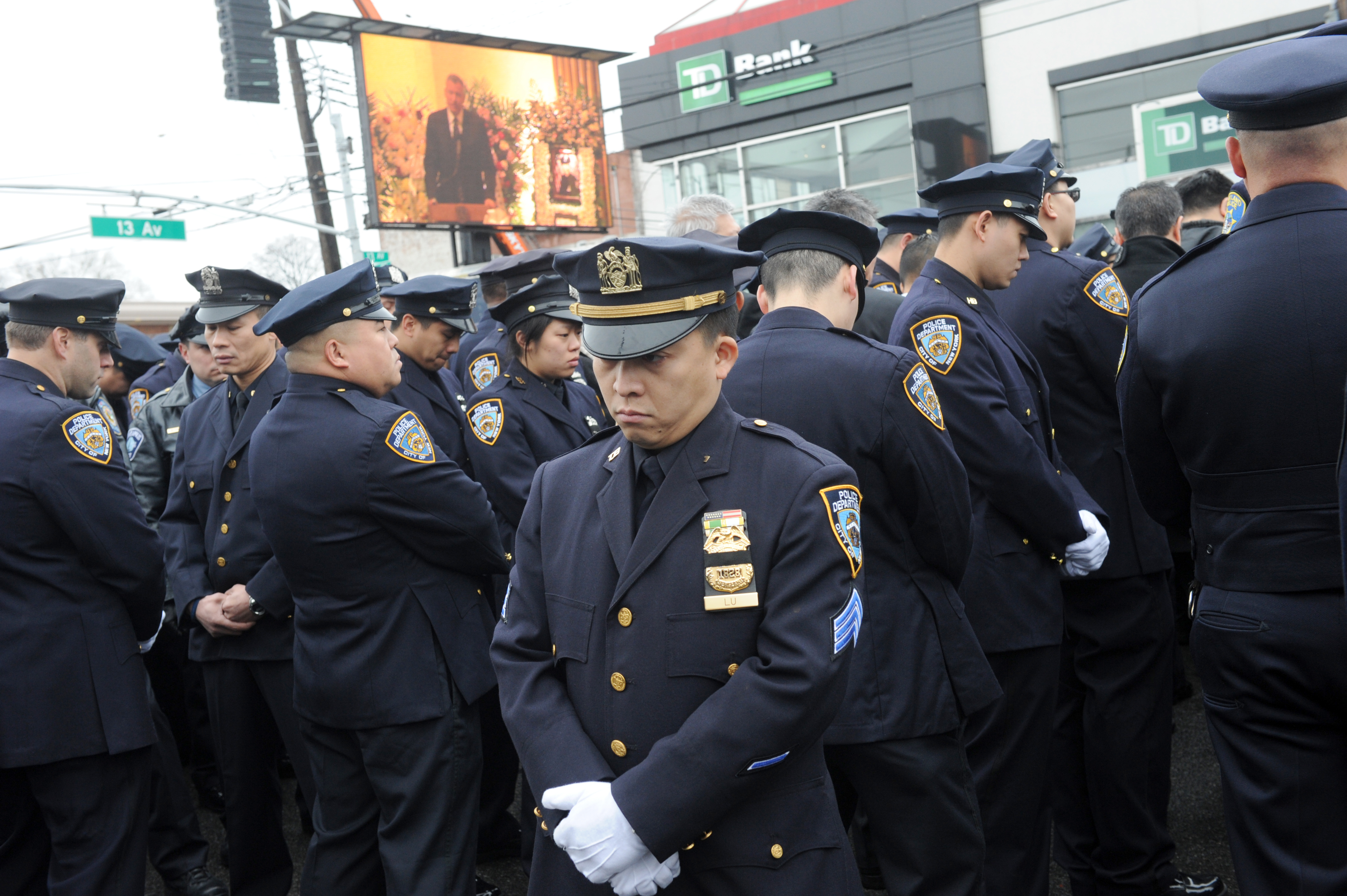 Police turn their backs to Mayor Bill de Blasio (on screen in bkgd) as he speaks at funeral of NYPD cop Wenjian Liu,32, at Aievoli Funeral Home in Bensonhurst .