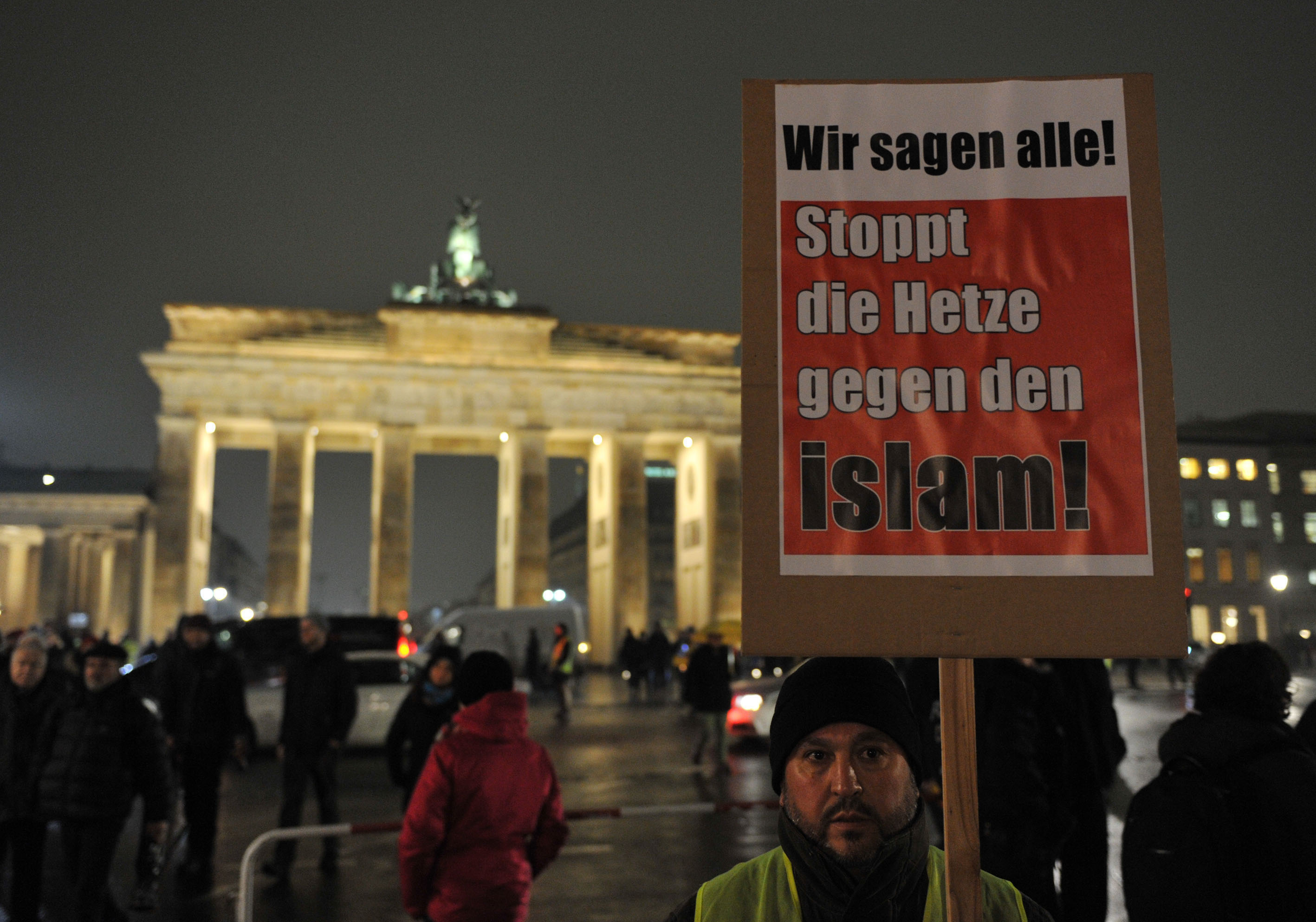 A man holds a placard reading  We all say, stop the hate against Islam  during a protest against Pegida movement in Berlin, Germany on January 05, 2015.