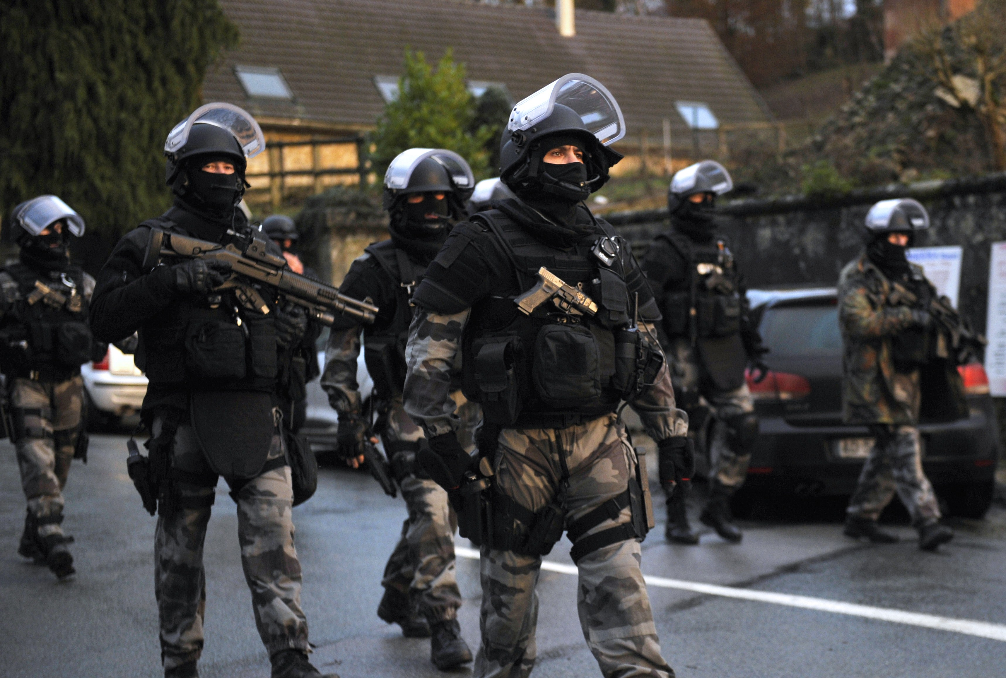 Members of the GIPN and RAID, French police special forces, walk in Corcy, northern France, on January 8, 2015 as they carry out searches as part of an investigation into a deadly attack the day before by armed gunmen on the Paris offices of French satirical weekly Charlie Hebdo.