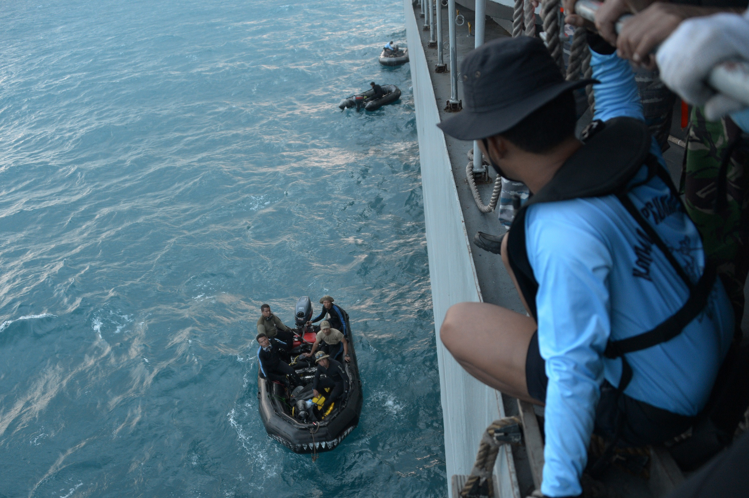 Indonesian navy divers, left, prepare to depart from the vessel KRI Banda Aceh to conduct operations to lift the tail of AirAsia Flight QZ 8501 in the Java Sea on Jan. 9, 2015