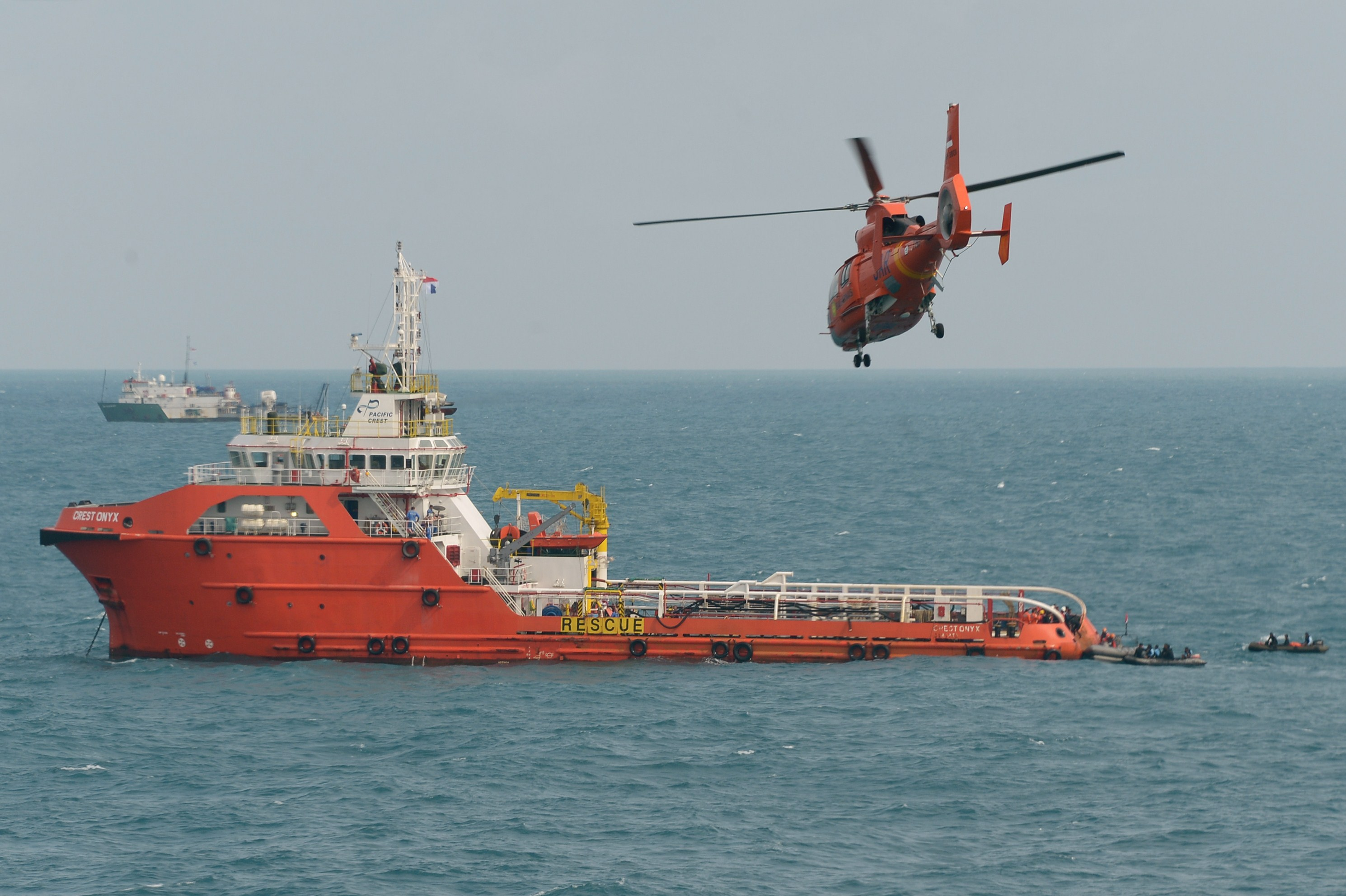 An Indonesian rescue helicopter flies over the Crest Onyx ship as divers (R in rubber boats) conduct operations to lift the tail of AirAsia QZ8501 in the Java Sea on January 9, 2015.