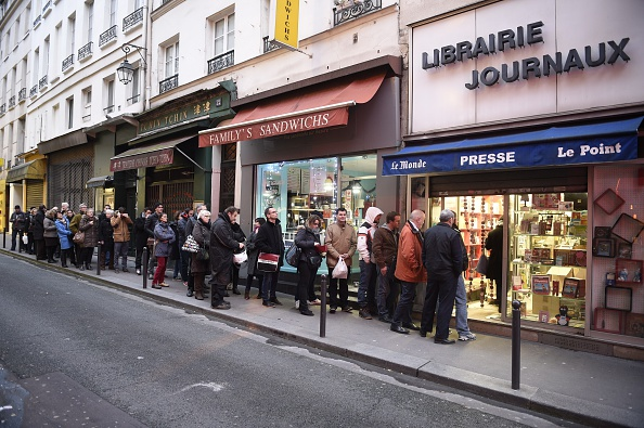 People wait outside a newsagents in Paris on Jan. 14, 2015 as the latest edition of French satirical newspaper Charlie Hebdo goes on sale.