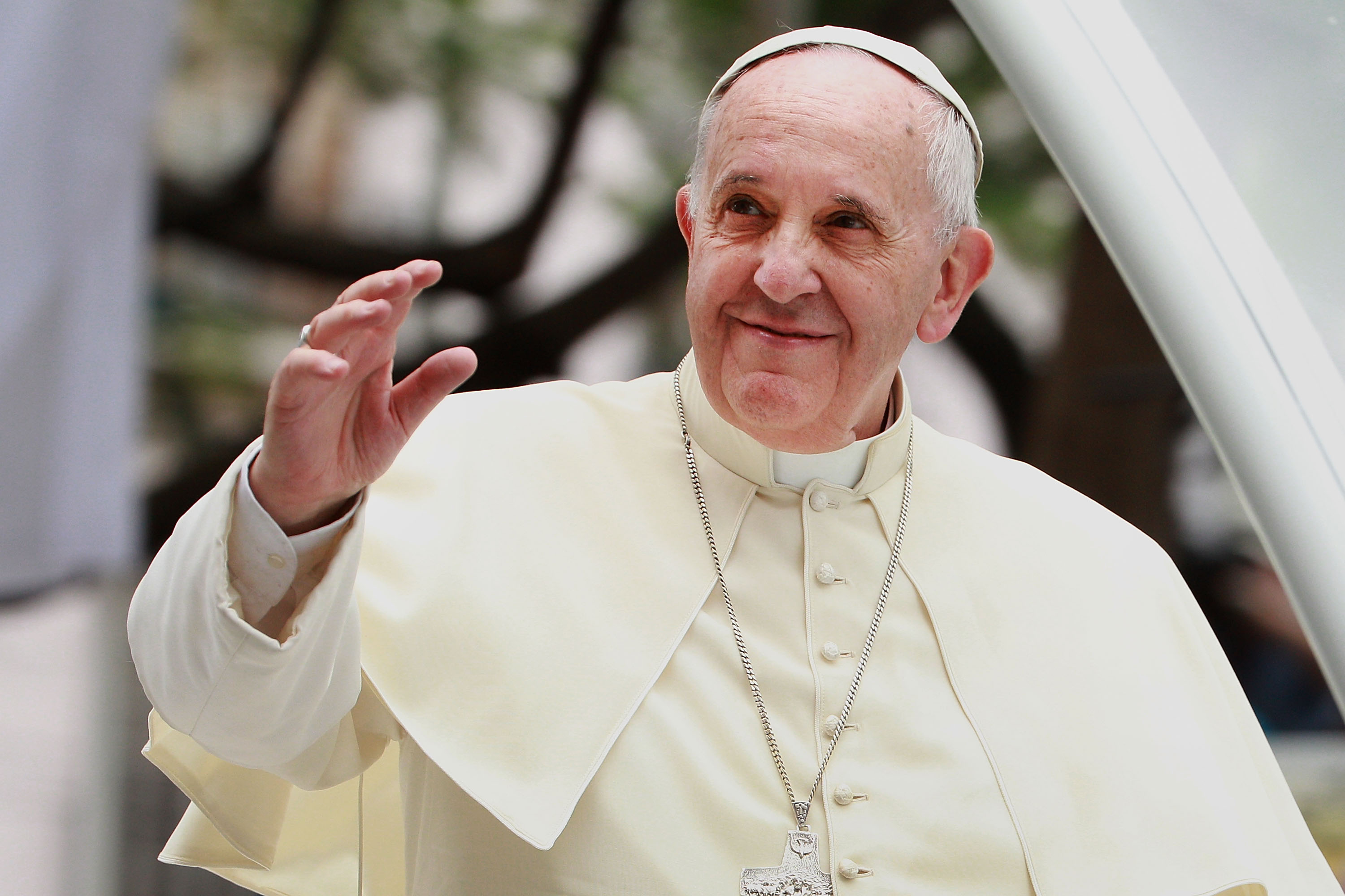 Pope Francis waves to thousands of followers as he arrives at the Manila Cathedral on Jan. 16, 2015, in Manila