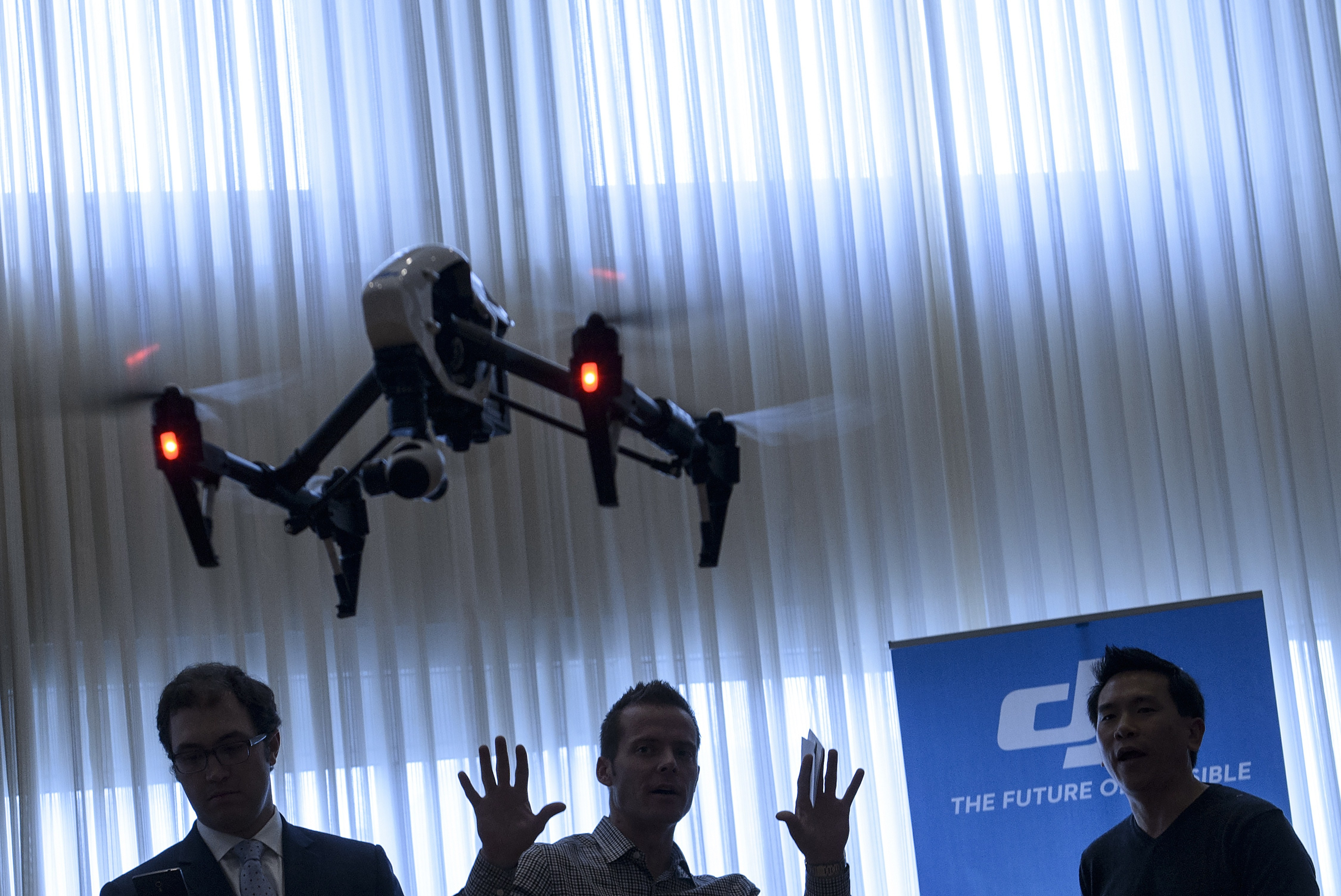 Staff from aerial imaging company DJI, demonstrate a remote control aircraft during a press conference by the Small UAV Coalition January 20, 2015 in Washington, DC.