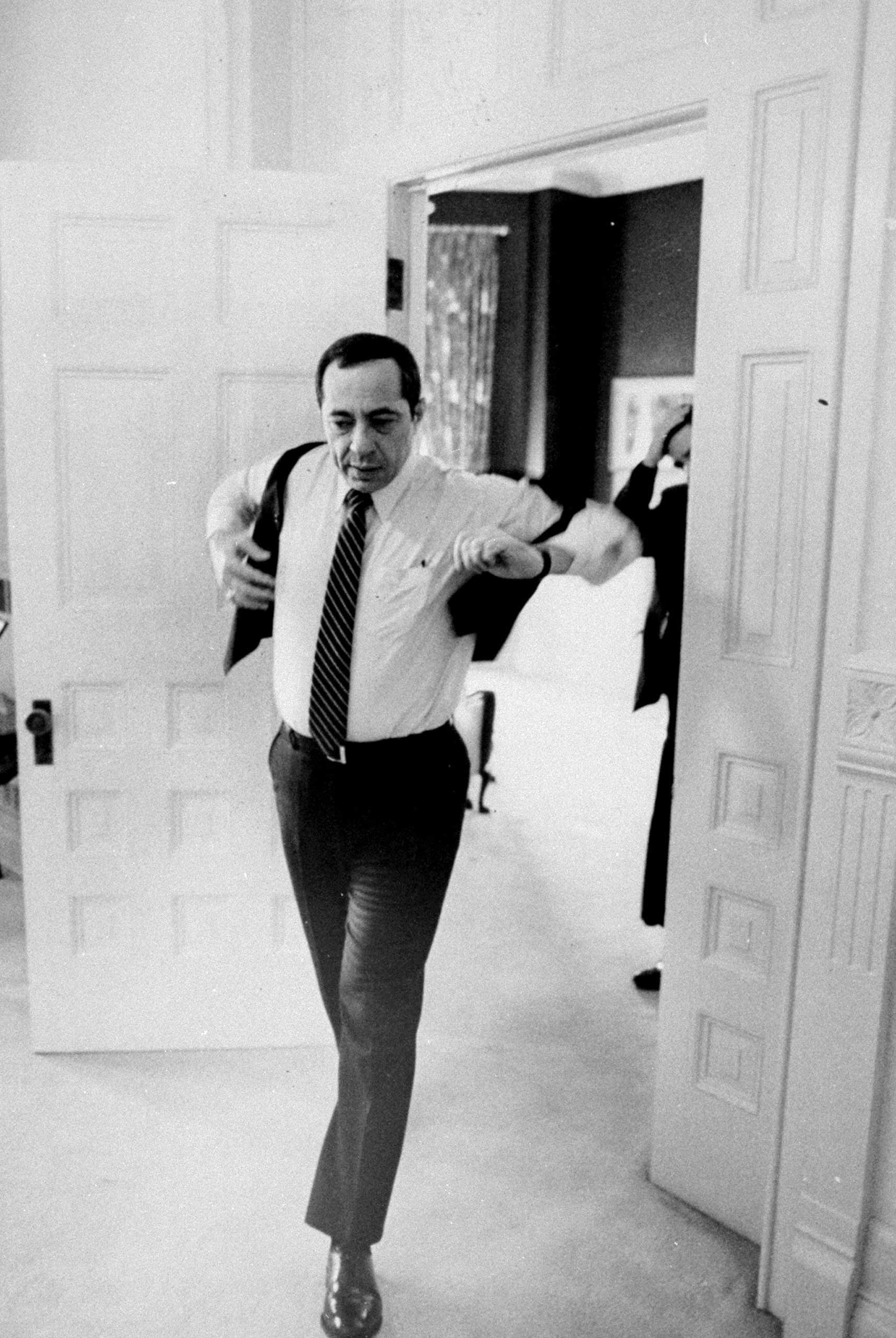 Gov. Mario Cuomo puts on a vest as he leaves his office at the Capitol in Albany, N.Y. on Jan. 20, 1983.