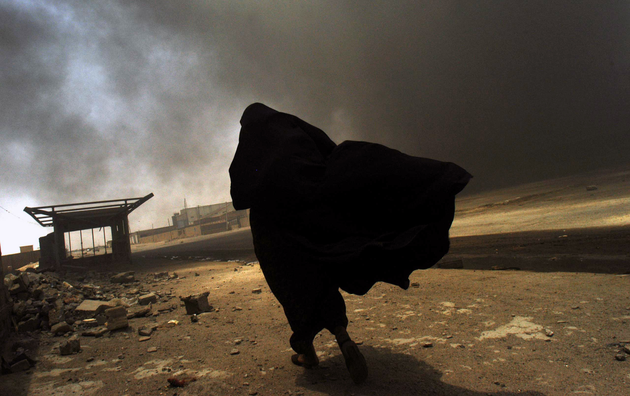 American Photo: The Influencers: Lynsey AddarioAn Iraqi woman walks through a plume of smoke rising from a massive fire at a liquid gas factory as she searches for her husband in the vicinity of the fire in Basra, Iraq, May 26, 2003.