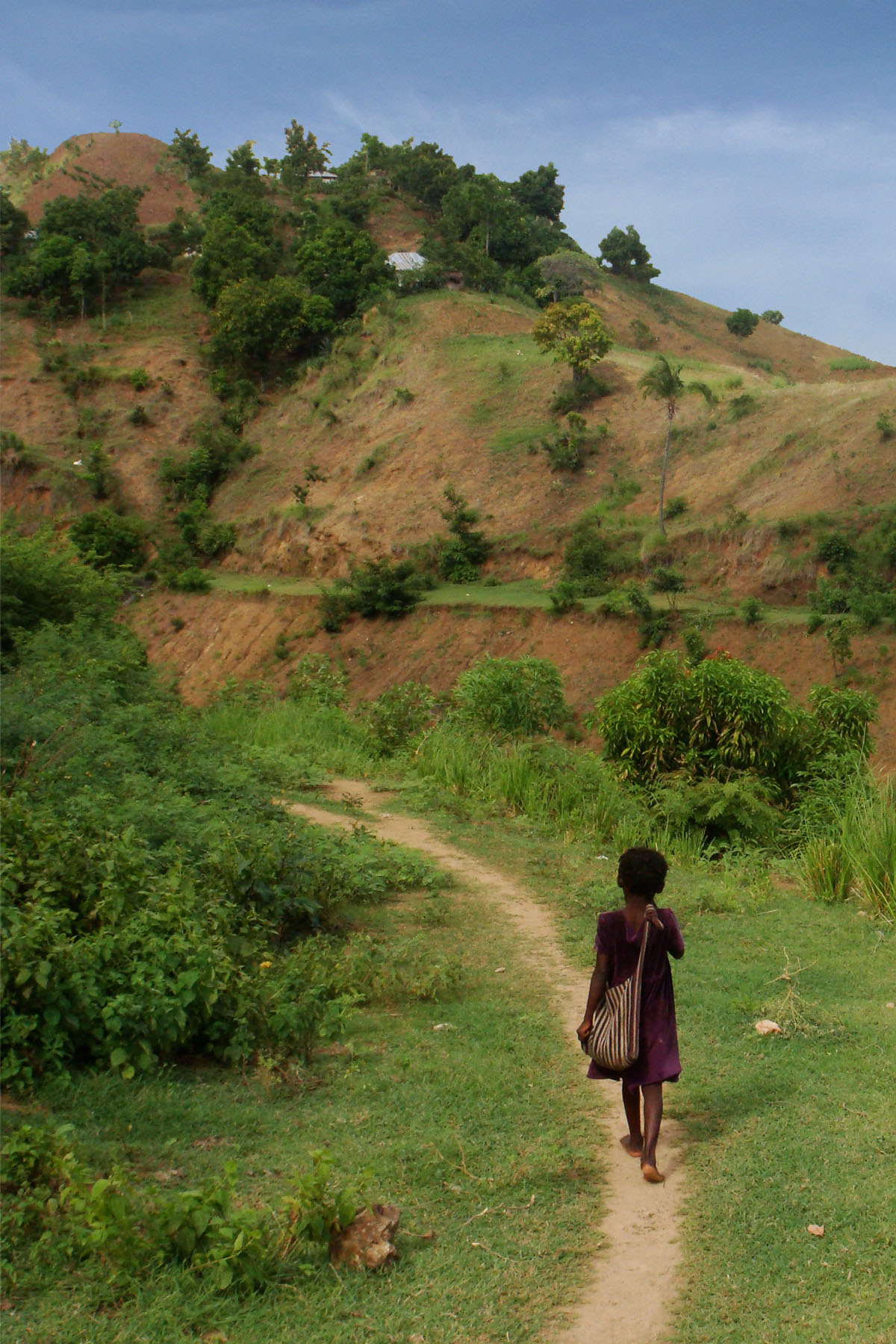 A girl walks along a path on her way to school in the upper watershed of Les Anglais. Until recently, there had been no maps showing where the schools are located, how many students attended, or any other critical information for improving schools facilities.