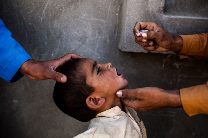 Health workers vaccinate a child for polio, a highly contagious virus, during the National Immunization Days in Jalalabad, Afghanistan.