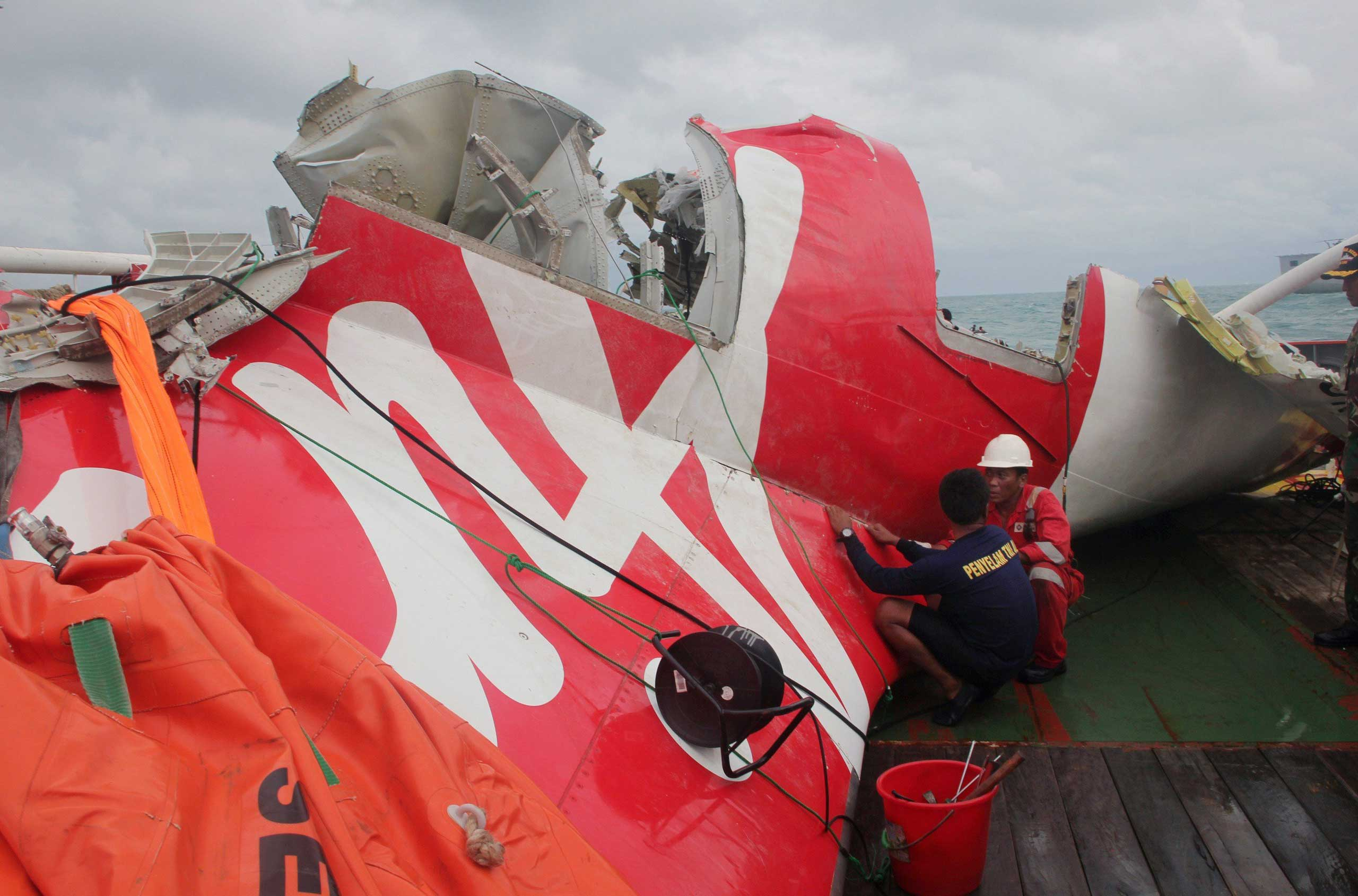 An Indonesian diver and an official examine the wreckage from AirAsia flight QZ8501 after it was lifted into the Crest Onyx ship at sea, near Indonesia on Jan. 10, 2015.