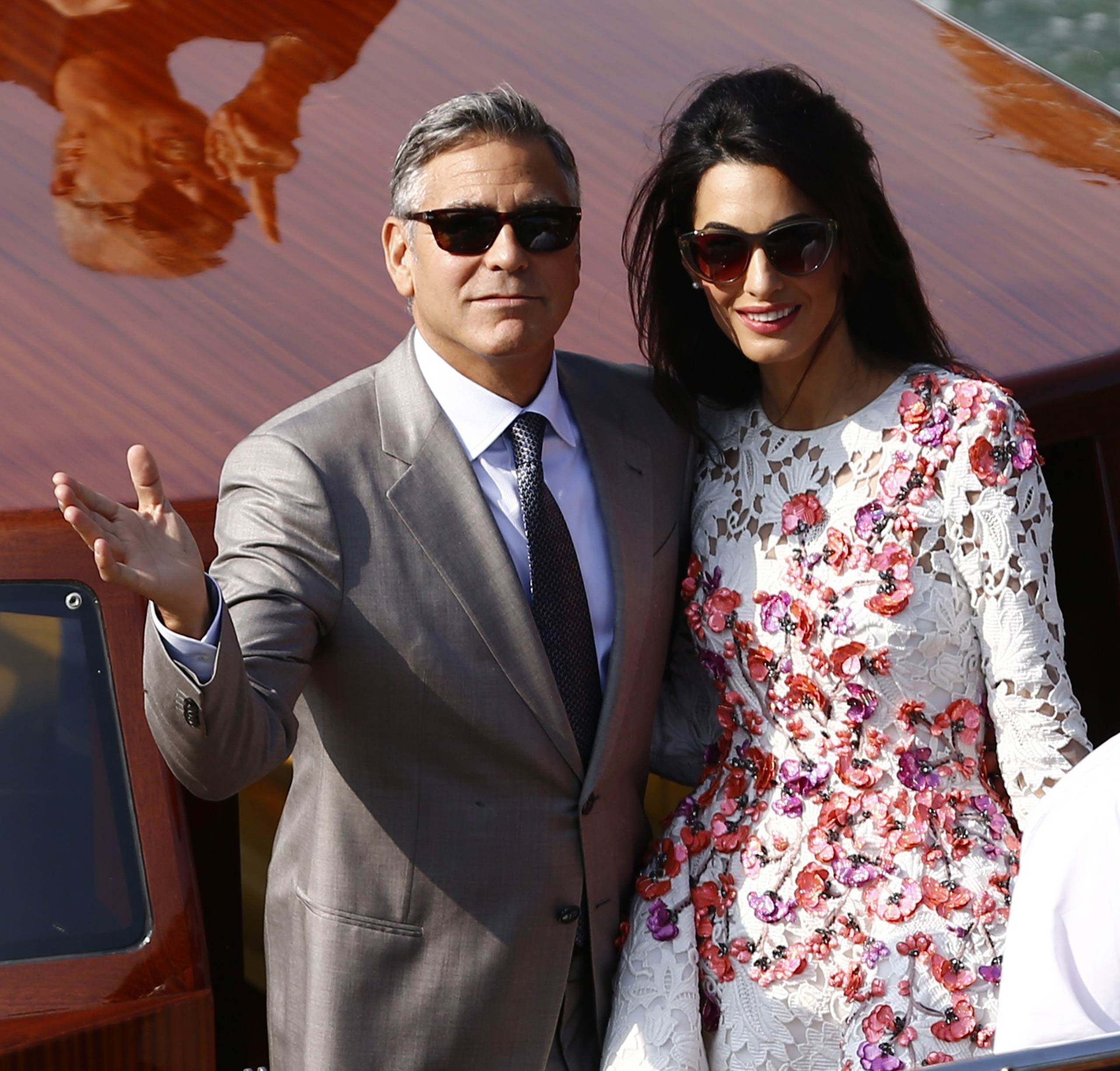 George and Amal Clooney stand on a taxi boat on the Grand Canal in Venice on Sept. 28, 2014.