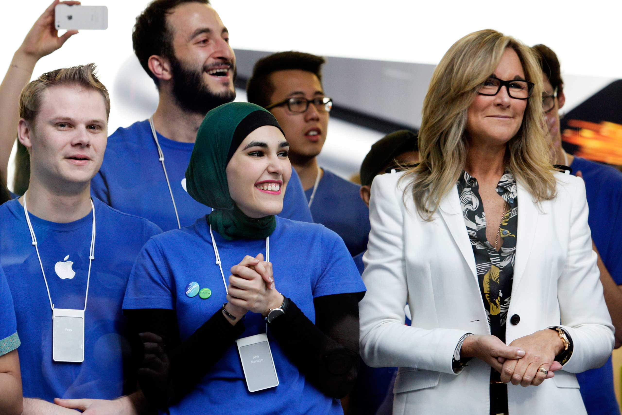 Angela Ahrendts, senior vice president of retail and online stores at Apple Inc., right, and employees look on before opening the doors to the company's George Street store for the sales launch of the iPhone 6 and iPhone 6 Plus in Sydney on Sept. 19, 2014.