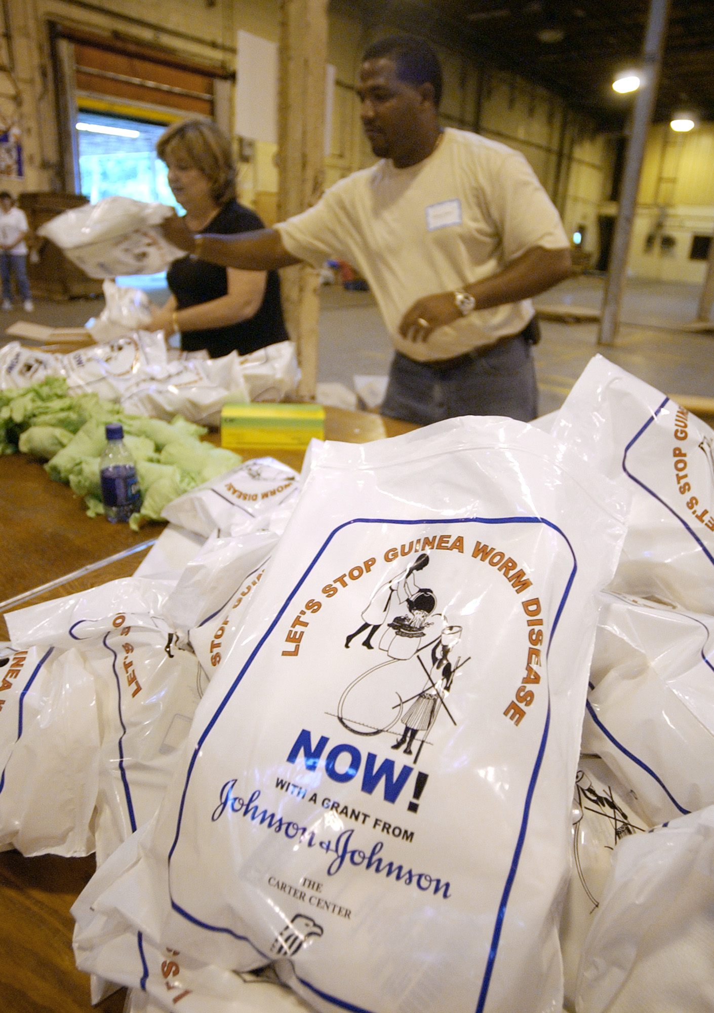 Volunteers Moises Matos and Helen Hand help assemble medical kits to fight Guinea worm disease at a warehouse on July 28, 2004 in Atlanta.