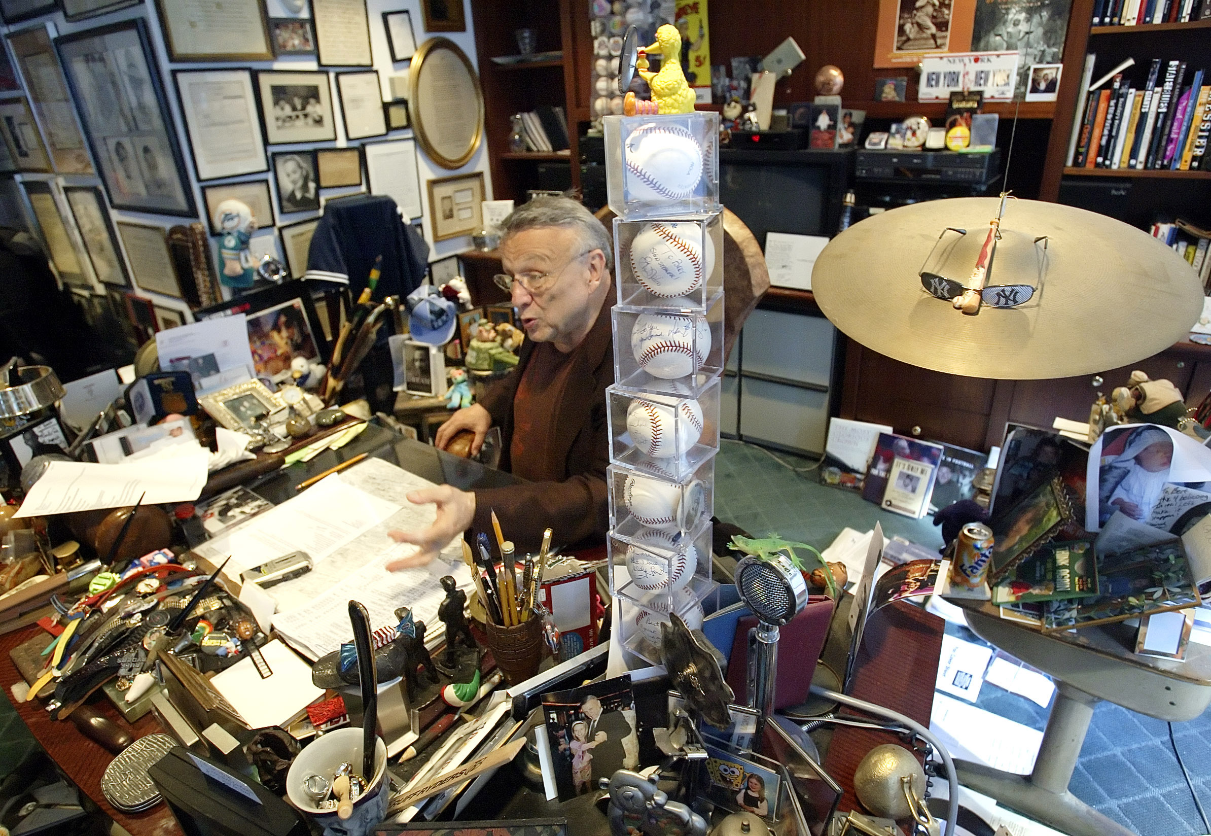 Bert Padell talks behind a tower of signed baseballs on his desk in his office in New York on Sept. 28, 2005.