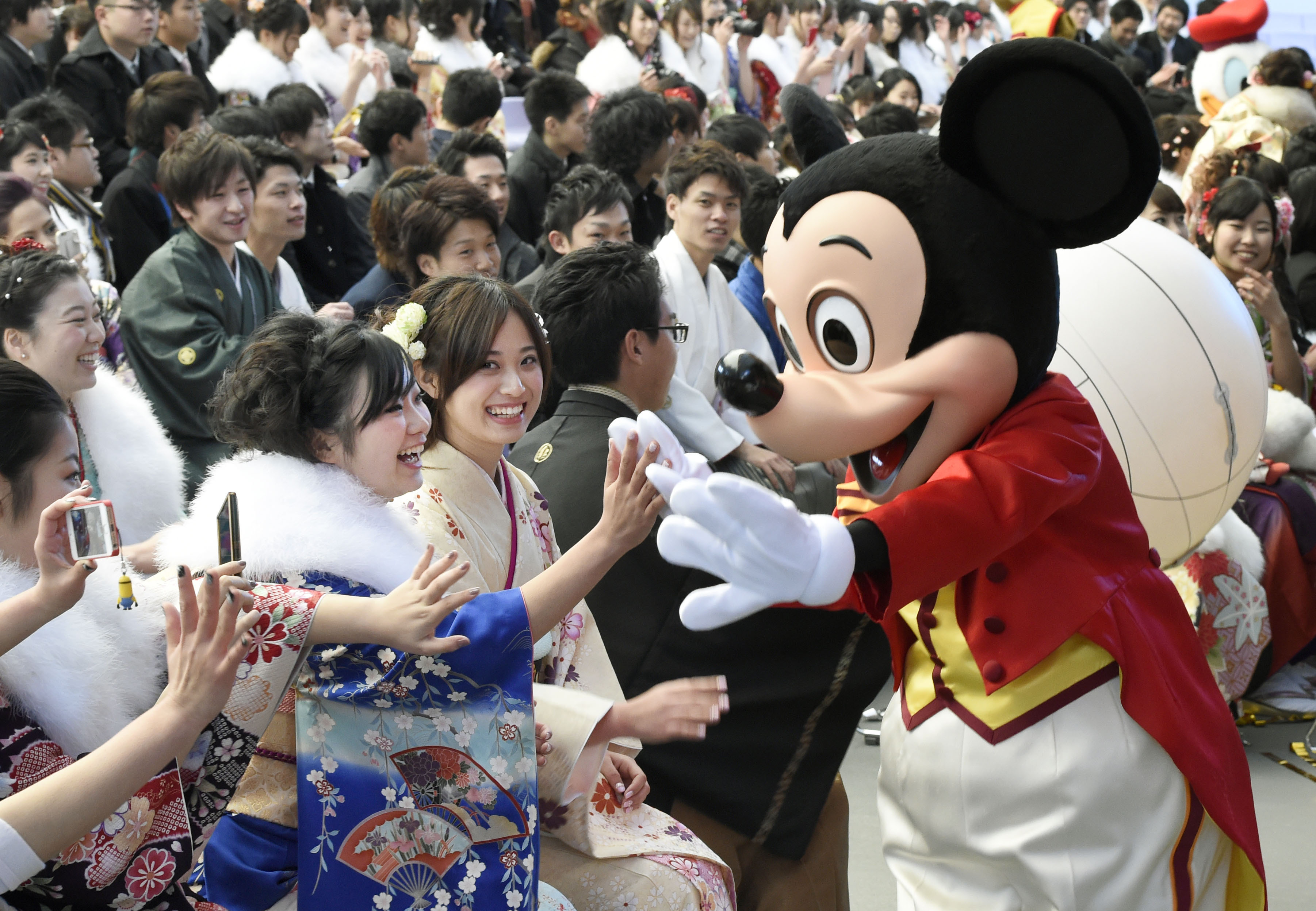 Mickey Mouse congratulates those who attended a coming-of-age ceremony at Tokyo Disneyland in Urayasu, near Tokyo, Japan, on Jan. 12, 2015