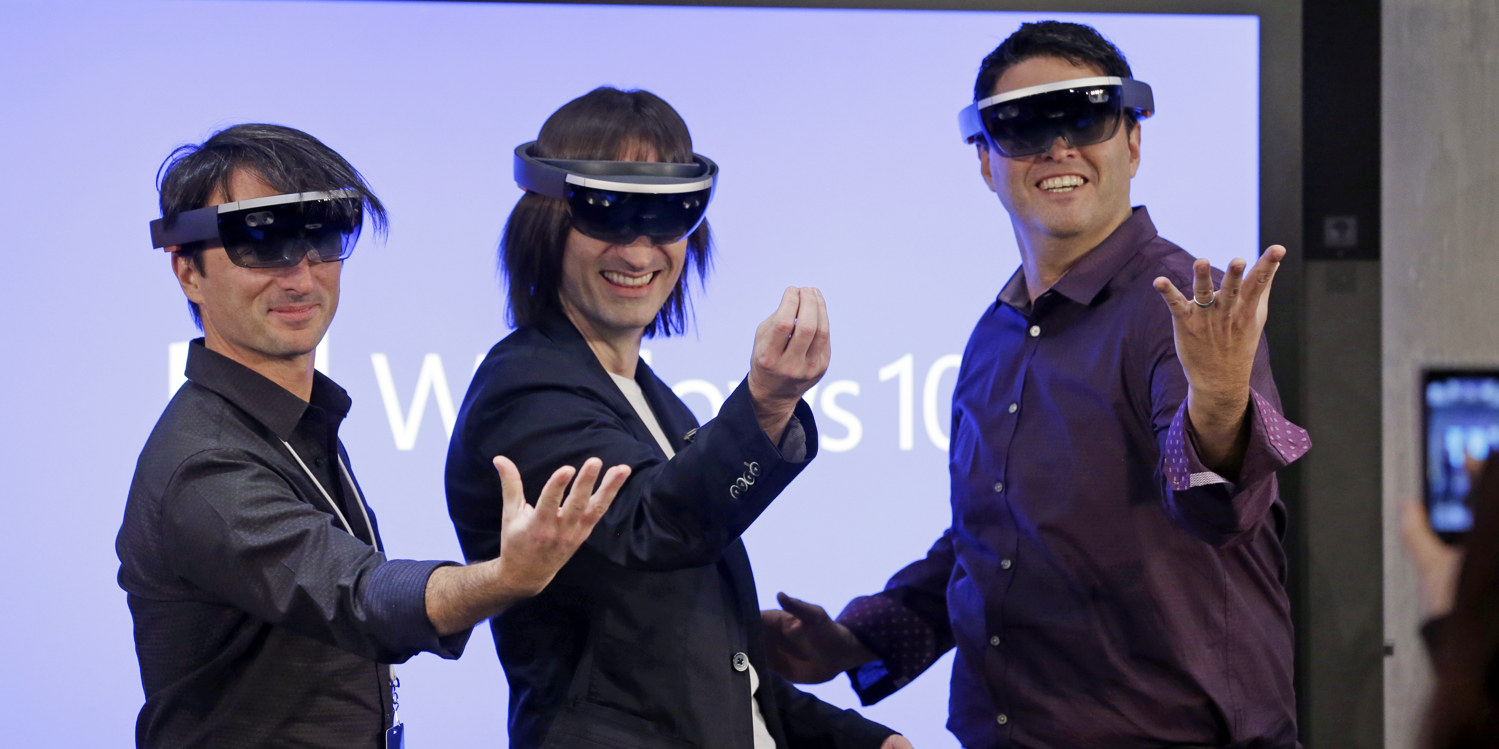 Microsoft's Joe Belfiore, from left, Alex Kipman, and Terry Myerson playfully pose for a photo while wearing Hololens devices following an event demonstrating new features of Windows 10 at the company's headquarters on Wednesday, Jan. 21, 2015