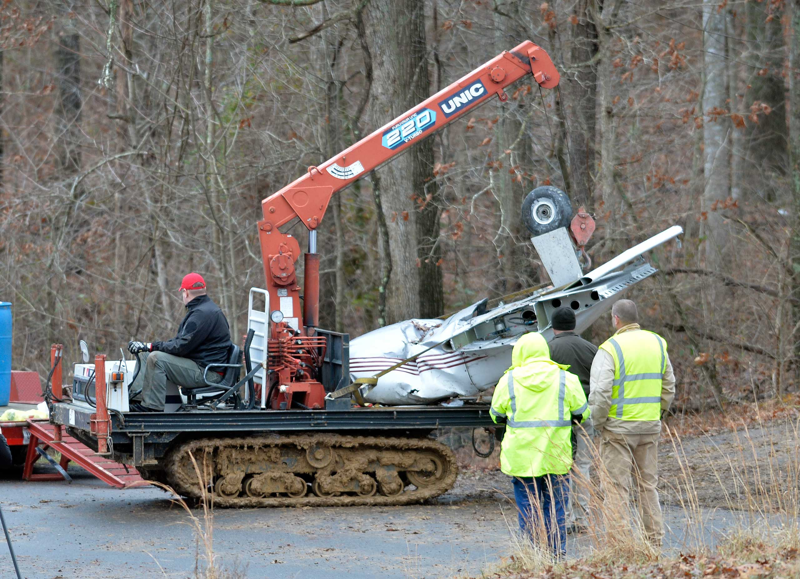 Salvage workers bring out part of a Piper PA-34's fuselage, wing, and landing gear from a crash site Jan. 4, 2015 in Kuttawa, Ky. Officials from the National Transportation Safety Board arrived at the crash site Sunday in Kentucky in which a 7-year-old girl survived and four of her family members were killed.