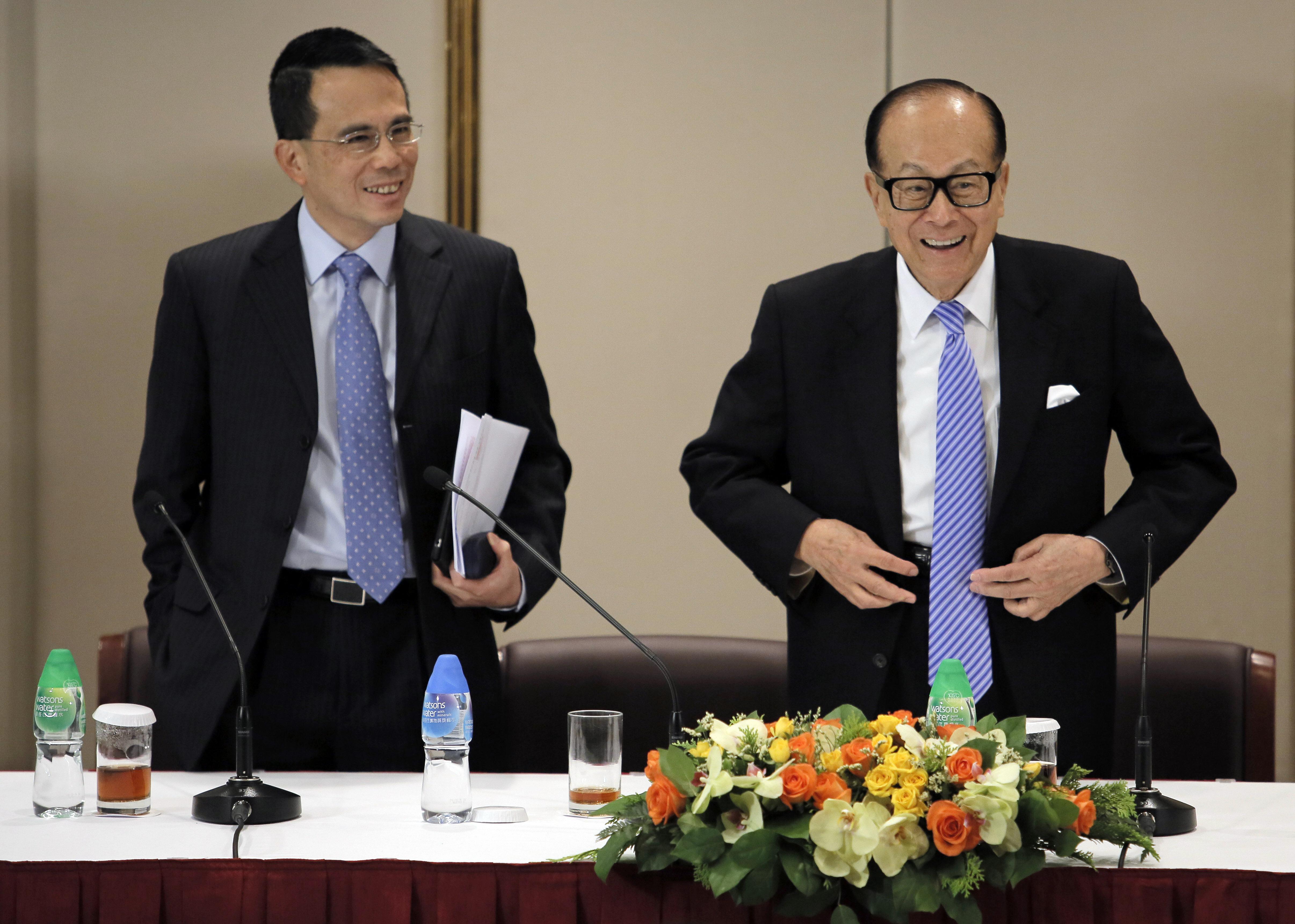 Hong Kong tycoon Li Ka-shing, right, and his son Victor Li, react during a press conference in Hong Kong Friday, Jan. 9, 2015.
