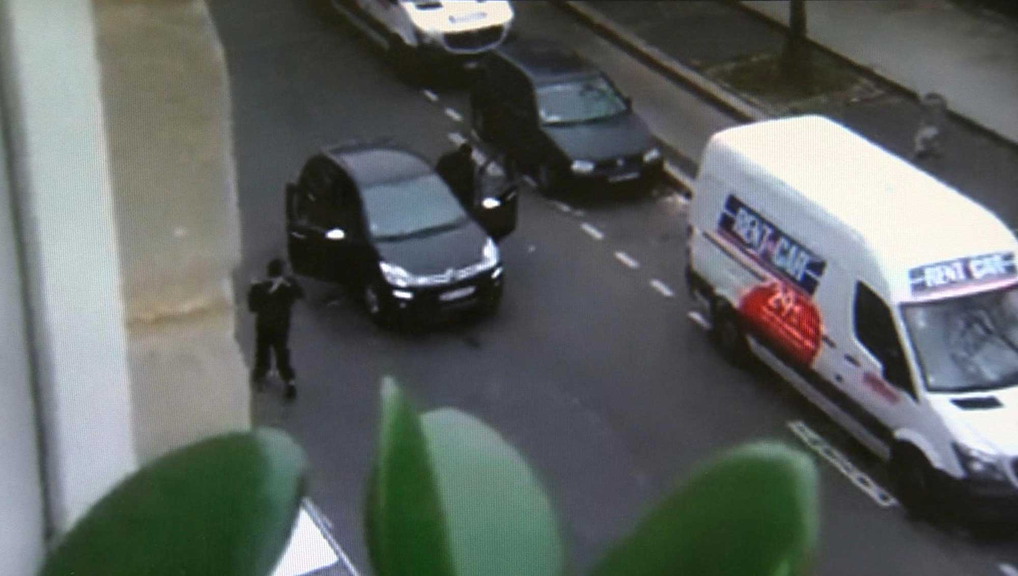 In this image made from amateur video recorded on Wed., Jan. 7, 2015 by Jordi Mir, masked gunman get into a car moments after shooting a police officer outside the offices of French satirical newspaper Charlie Hebdo in Paris.